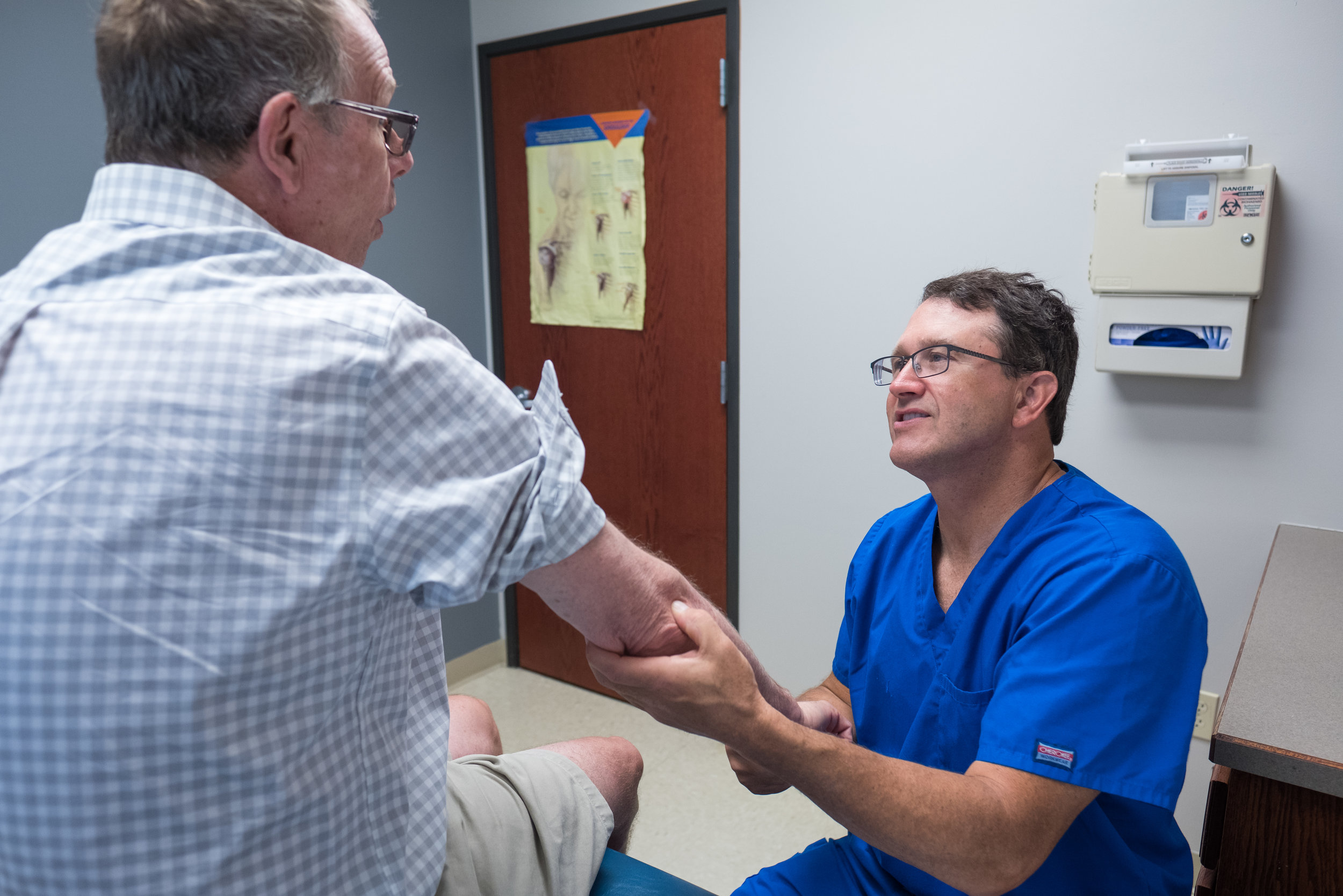 "Dr. Galbraith examining Greg's elbow. Greg received a cortisone shot and was diagnosed with ""tennis elbow""-likely caused by repetitive movements from sorting and delivering mail."