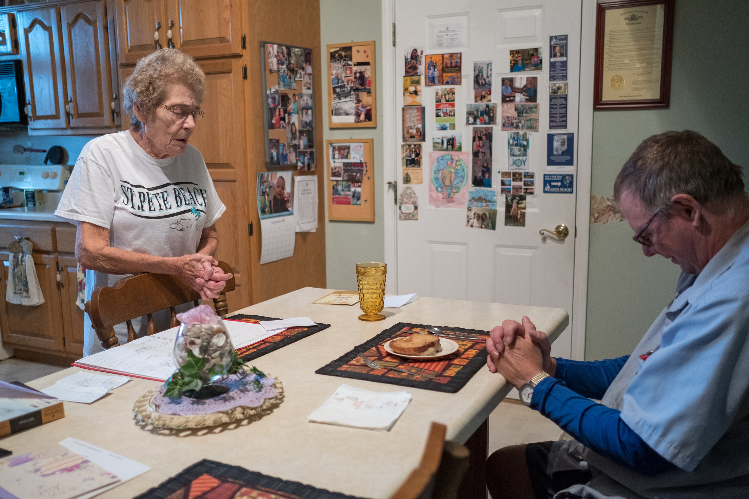 Greg and Ruth say a quick blessing before Greg eats. Ruth is 90 years old and benefits from Greg's regular visits.