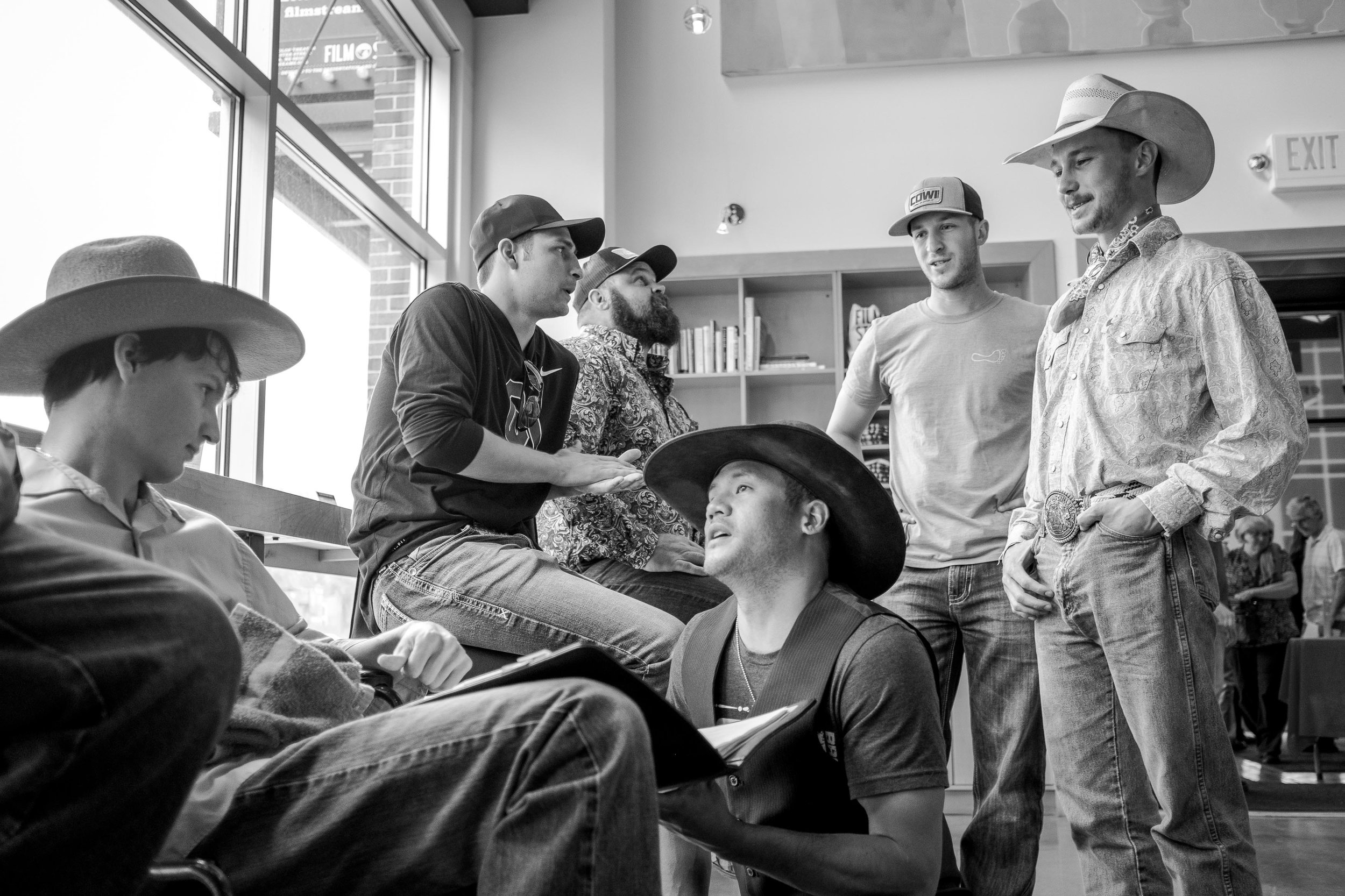 Lane Scott (far left) and Brady Jandreau (far right) catch up with rodeo friends before the screening of The Rider.