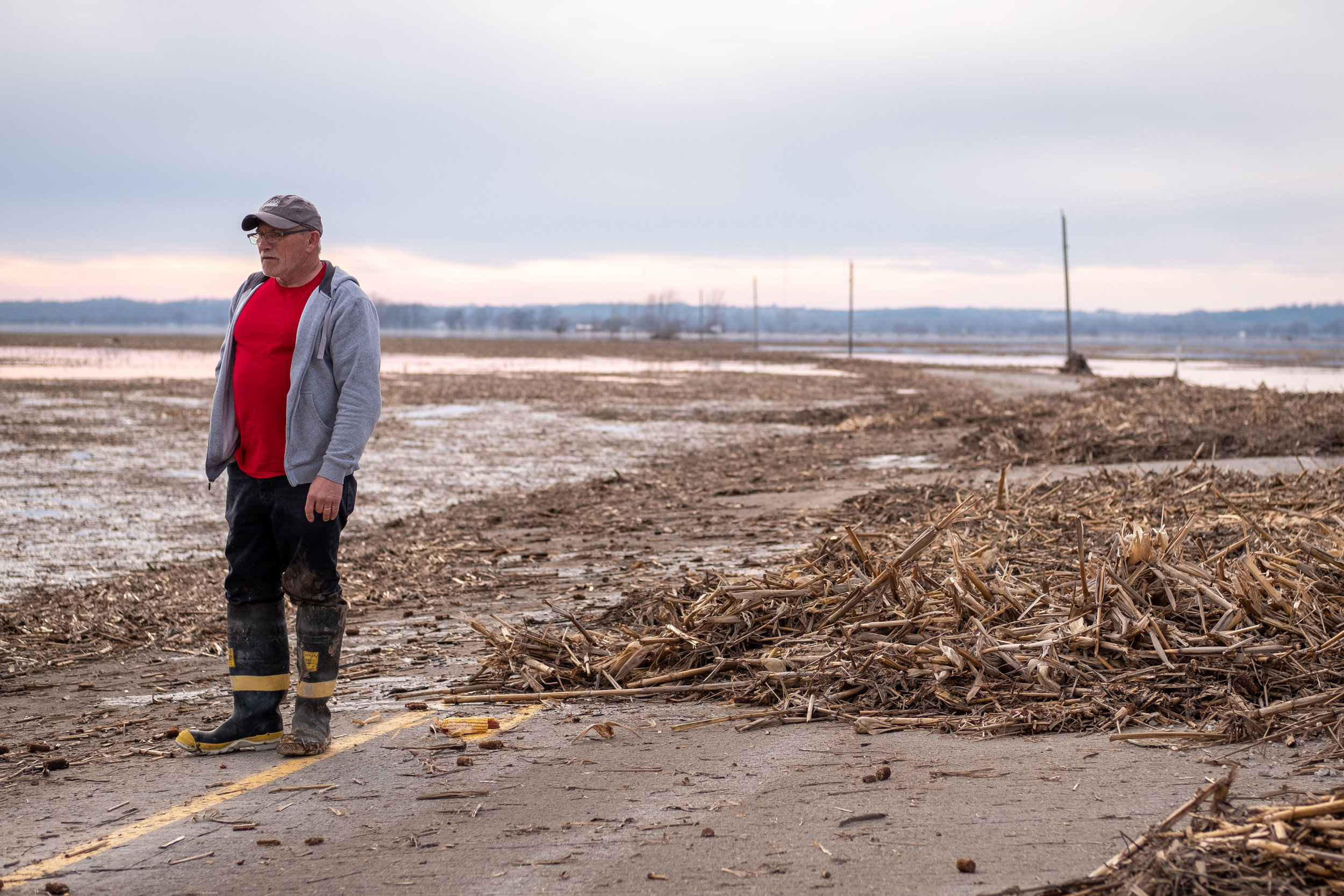 Dean Doty stands on the impassable road to Bartlett Iowa. Doty's home can be seen several miles to the west.