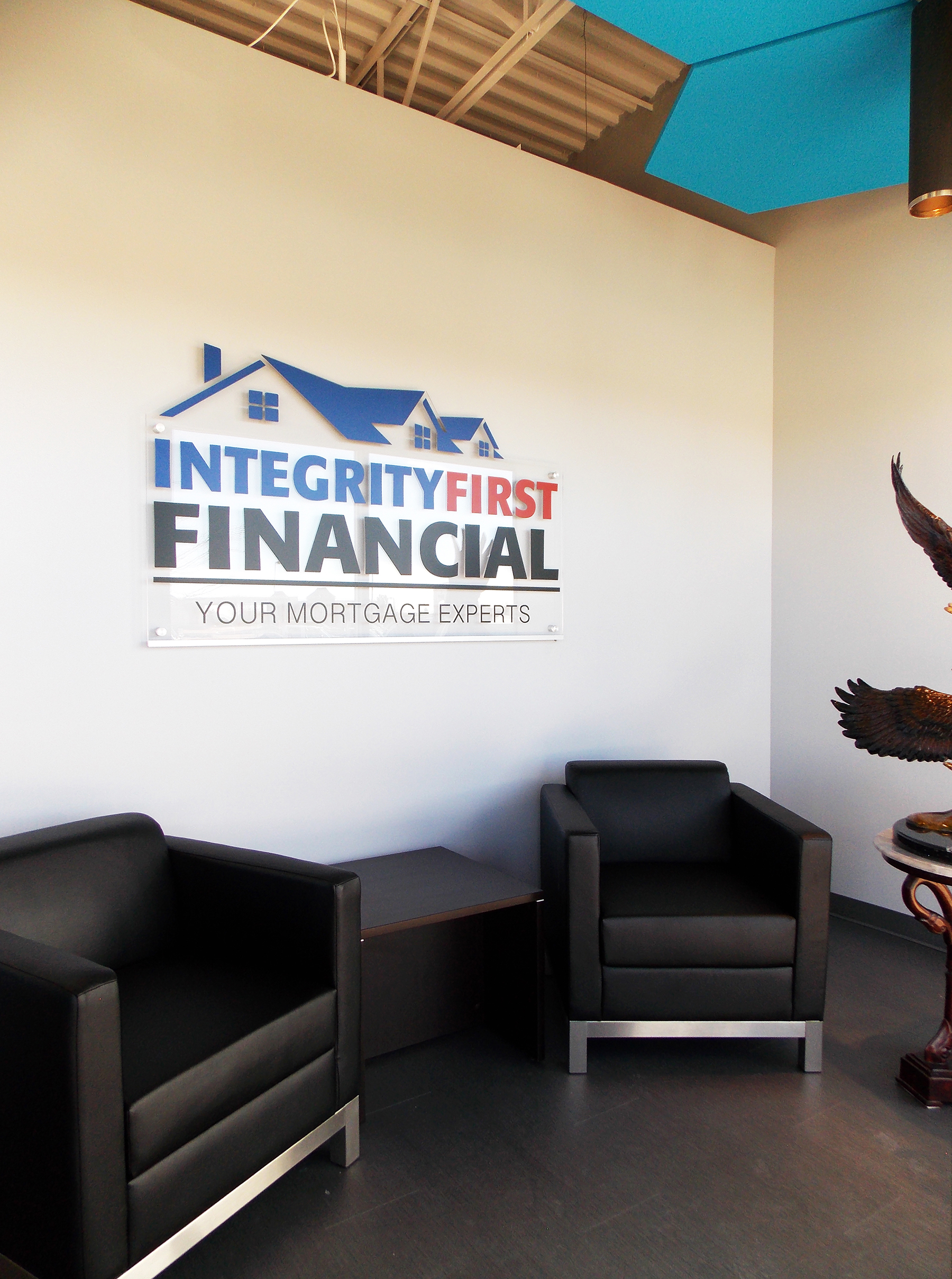 The entrance to Integrity features an efficient seating area with plenty of natural light and a large, LED backlit acrylic cut sign created by  Layer Nine Design . The open ceiling is visible above the walls to make the entire office feel more spacious.
