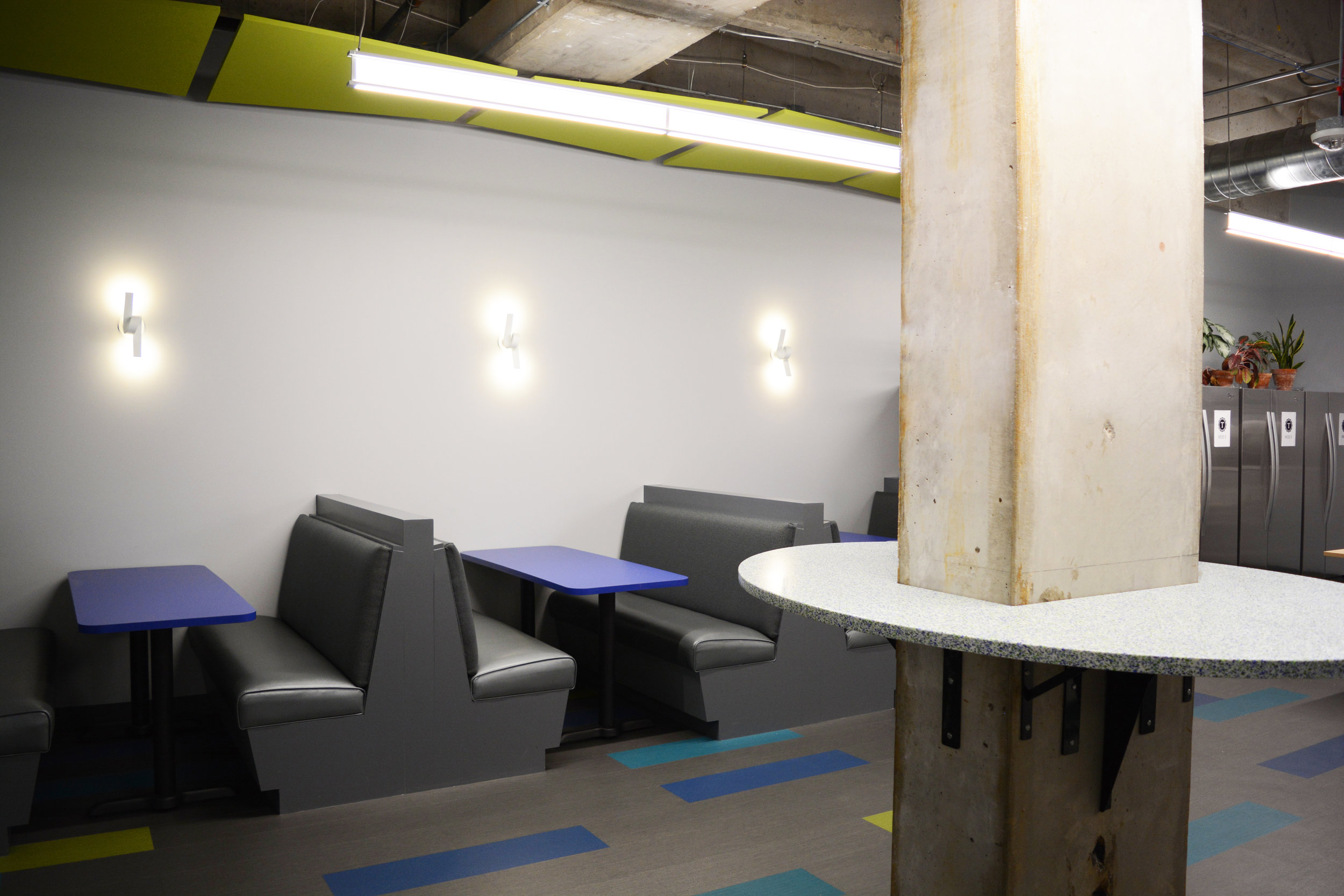 Turing is not the typical higher education campus but that didn't deter us from providing some campus style. The break room includes built-in banquettes and recycled glass countertops that enhance the bright color palette of the space by utilizing green and blue glass chips.