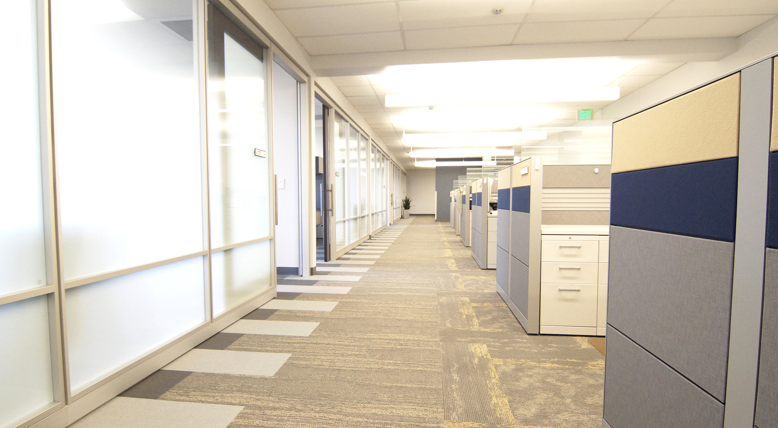 """Throughout the space, offices with glass fronts line the exterior of the floors, allowing natural light to filter into the open office interior where the workstations are installed. The carpet pattern is comprised of the three styles of  Mohawk's Iconic Earth  collection along with accents of blue installed in a """"zipper"""" pattern underneath the architectural wall system, weaving in and out of the private offices."""