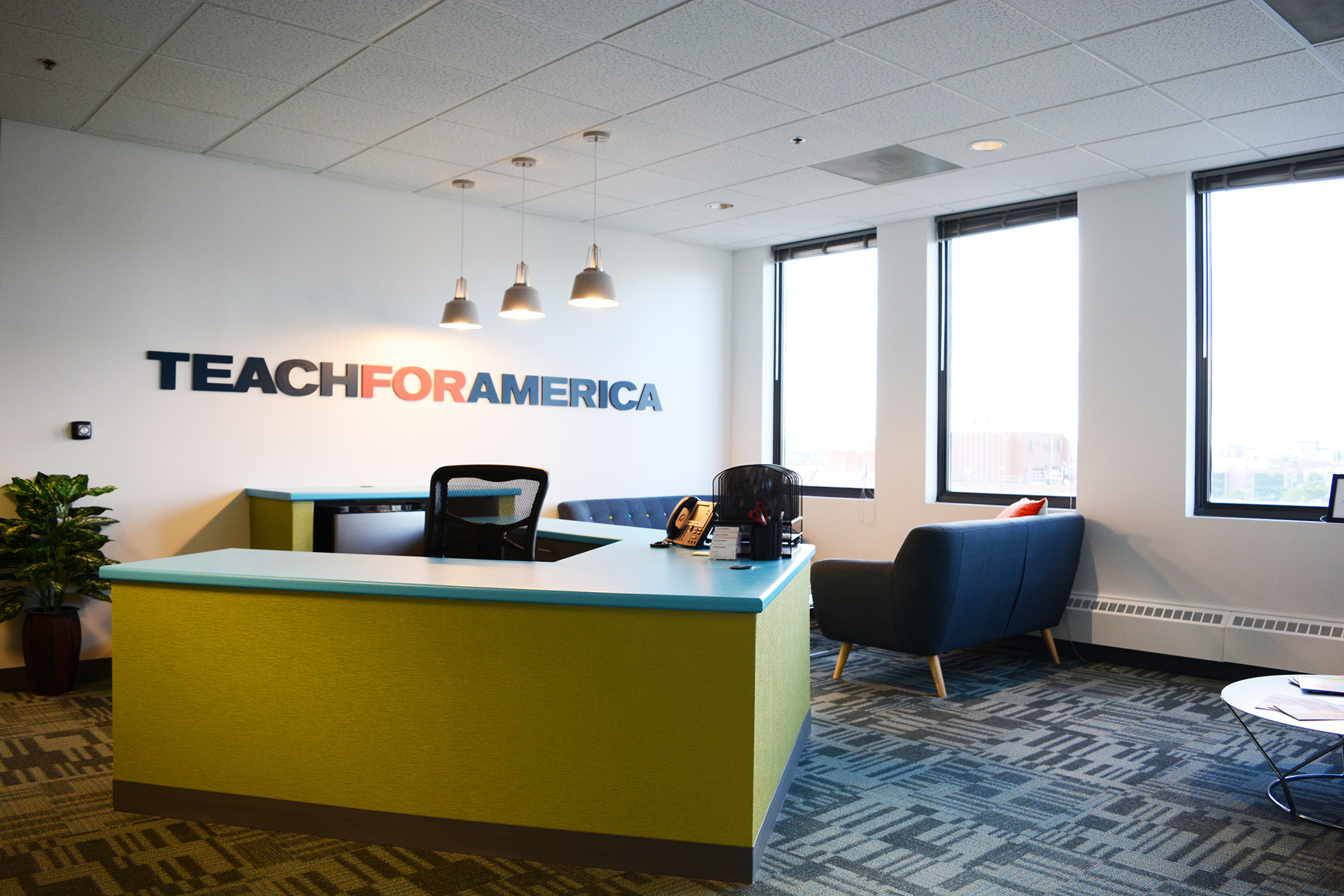 Teach for America wanted to have a casual and welcoming entry area that not only greeted guests with a cozy 'living room' feel, but could serve multiple purposes such as impromptu meetings and lounging. The diagonal placement of the desk allows for visitors to feel immediately welcomed even when a receptionist is not in sight.