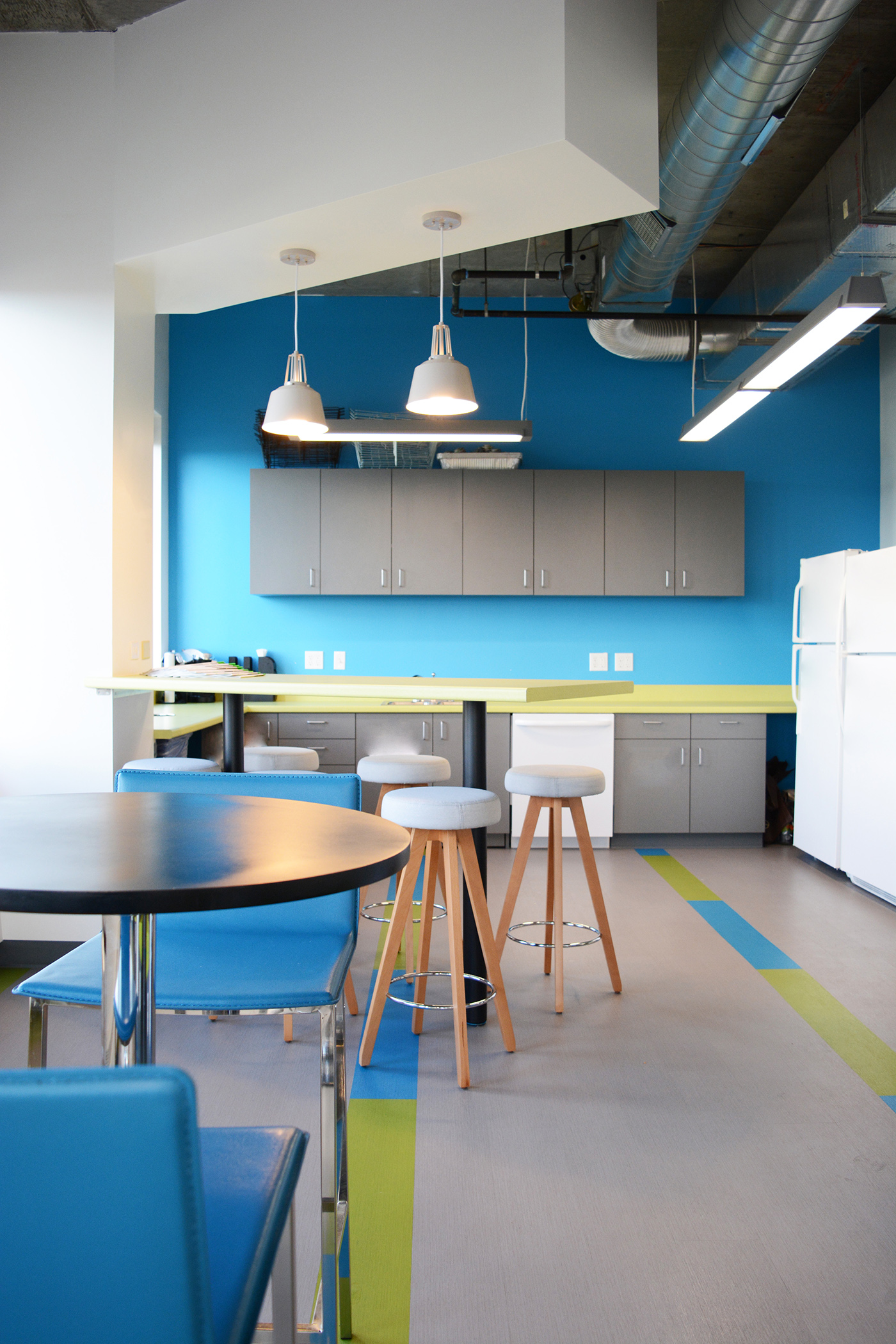 In response to Teach for America's lack of eating area and counter space, Kestrel designed a large L-shaped counter and added a bar height seating area. Colorful stripes of Shaw Pigment LVT were used to add interest to the floor and tie in the colors of the counter and accent paint. The seating area features telescoping doors that are painted with white board paint. These can be closed when a more private meeting is necessary or opened for a more casual feel.