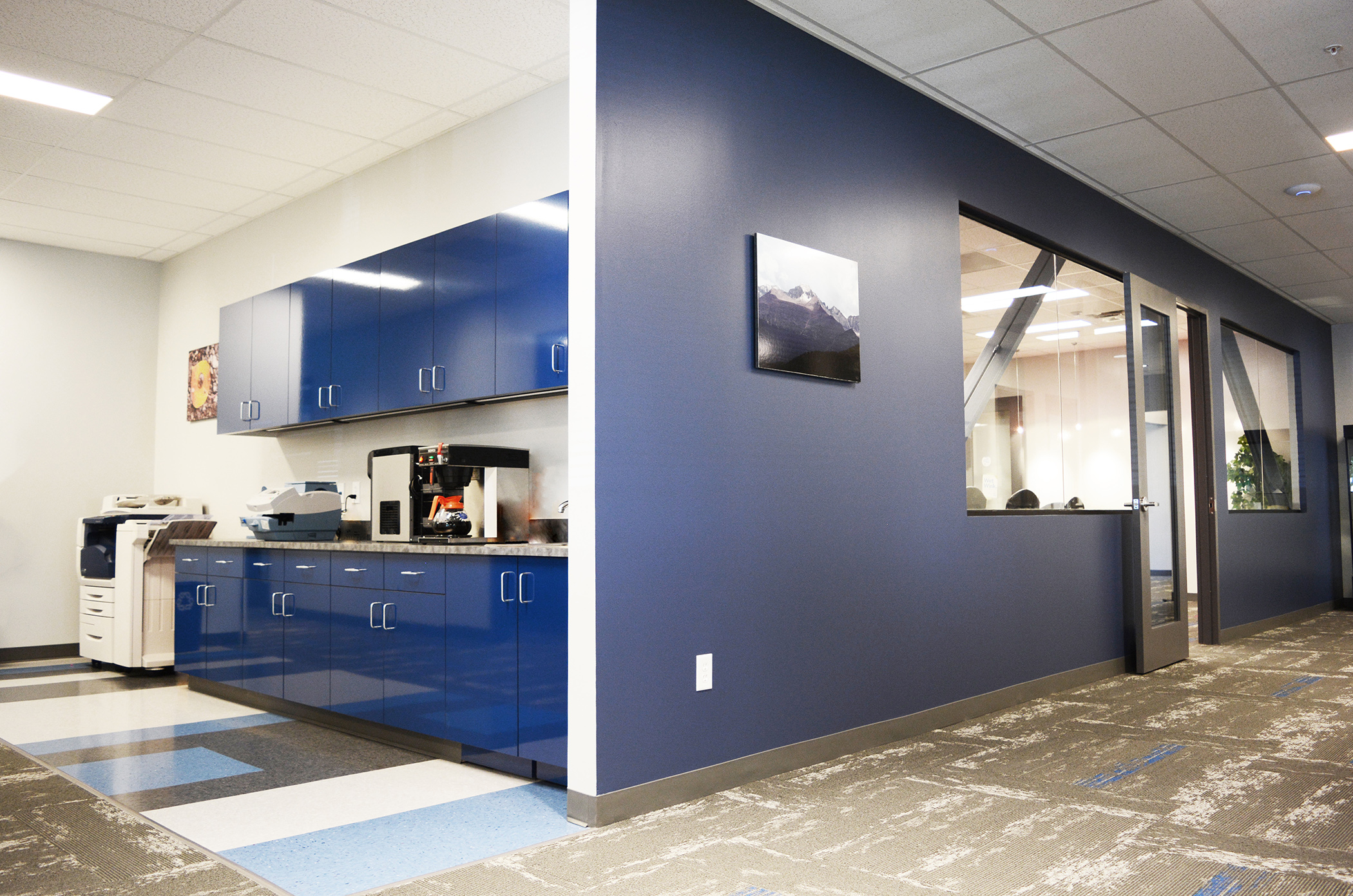 The executive hallway and private office corridor features a coffee bar, printing station and access to the board room with the painted cobalt metal bracing visible through glass sidelights.