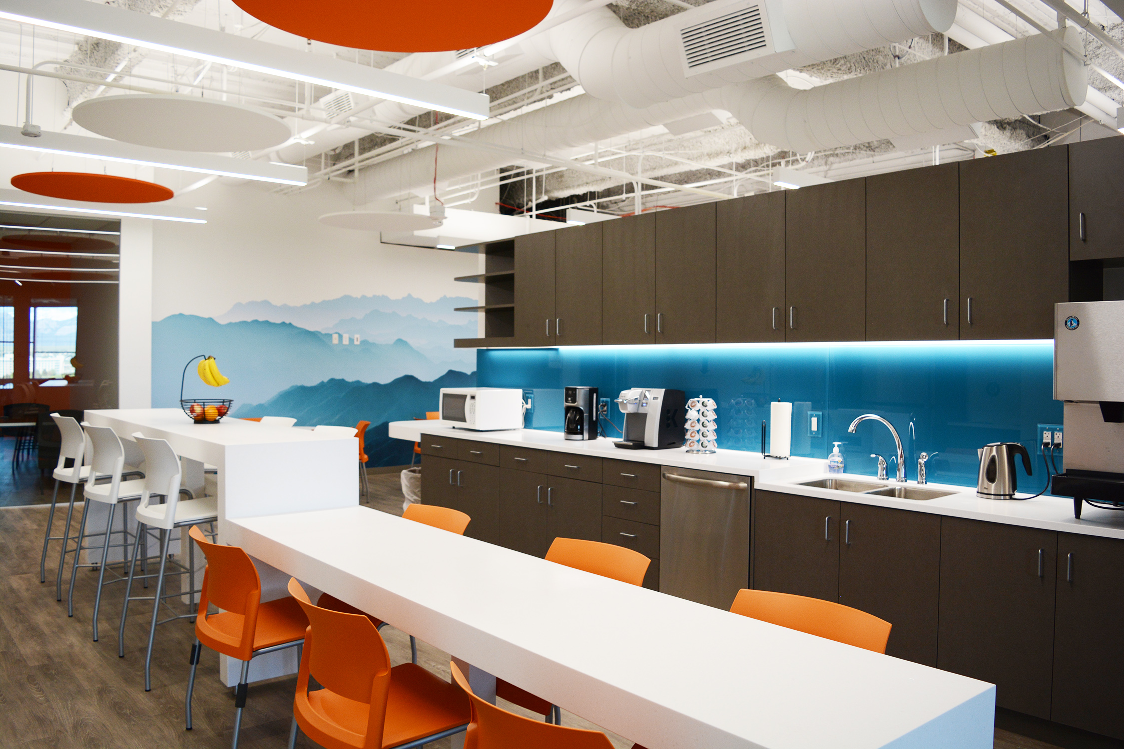 Employee attraction and retention, along with providing amenity driven spaces within the open office, were important factors in overall design. The break room ceiling was removed to create a large, bright and less corporate space. A dual-level  Corian  island was designed to be a place to grab a quick bite, have an informal meeting and provide space for catered meals. The back painted glass backsplash appears to glow from the undercabinet lighting and the white countertop adds a crisp delineation to the dark cabinets.