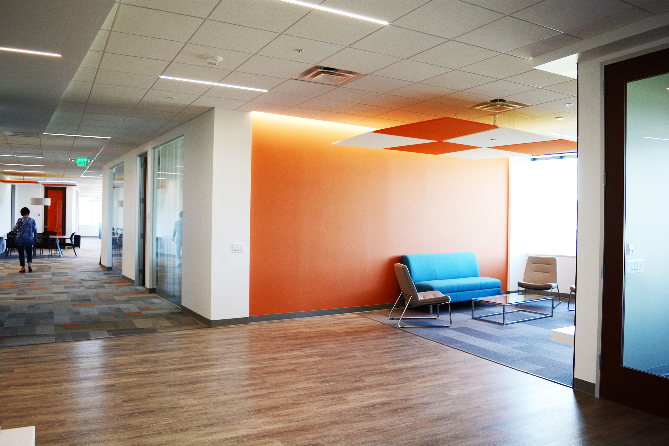 The reception and waiting space off the entry opens to an incredible view of the flatirons. To keep the area open, a small seating area occupies one corner in front of an Avoka orange wallcovering with subtle detail. As the space doubles as an informal meeting area, acoustical clouds were added to allow for more intimate conversation.