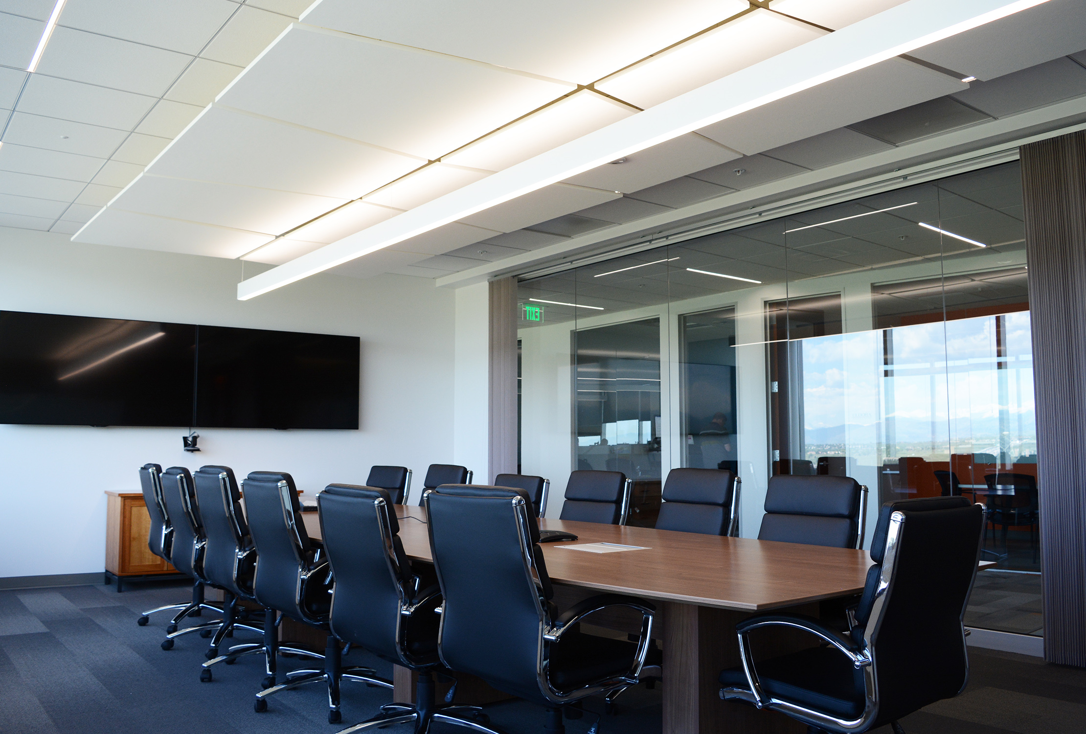The boardroom, located just off the entry, is afforded a prime location on the glass with mountain views, which is the main feature. The room remains classic and simple with  Armstrong  acoustical clouds for noise dampening and multiple light fixture types for interest as well as functionality depending on use.