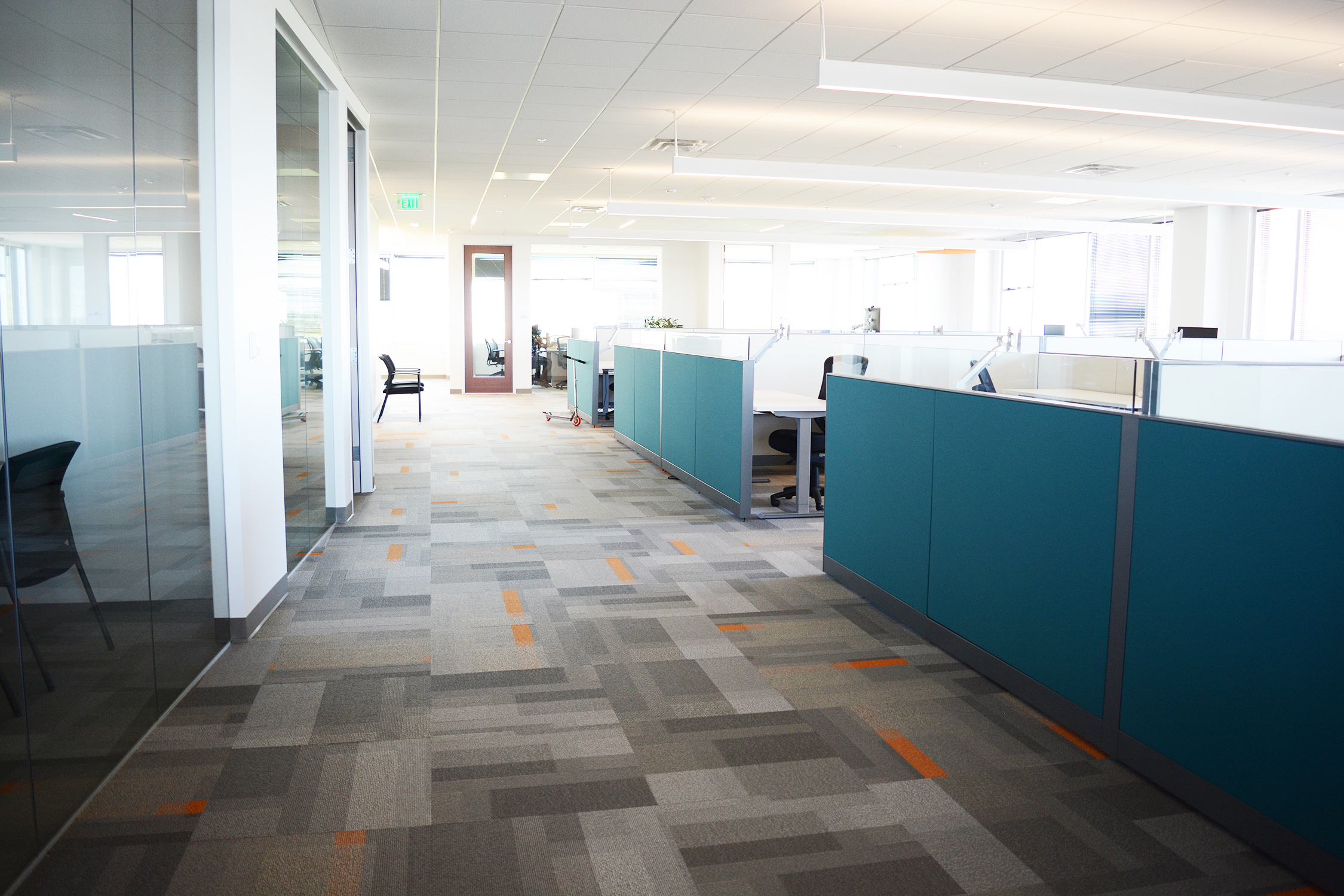 From the beginning, the approach to space planning was to provide all employees access to natural light and the mountain views. This was achieved by placing private glass front offices on the interior and utilizing workstations with glass privacy screens to allow light to filter within the open office. The teal end panels paired with  Patcraft's Color Pop  carpet add the final touch of branding needed throughout the office.