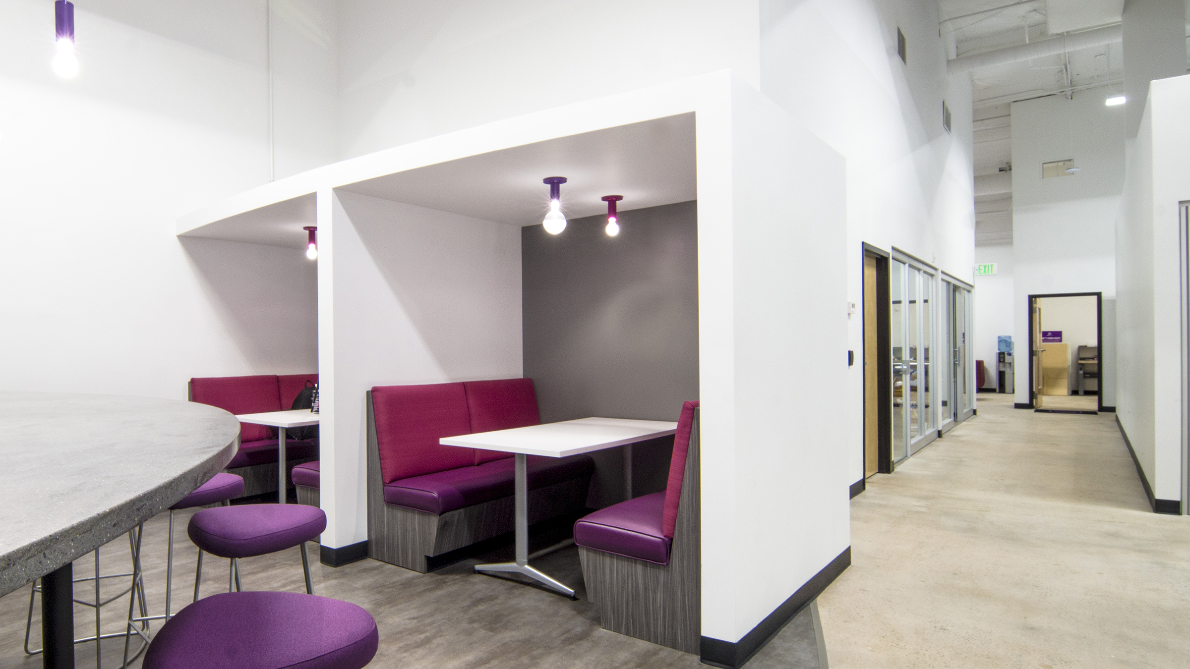 At the break room, Solderworks wanted to not just provide an area for storing and heating up lunches and snacks but an area with a sense of place. Additional tables and chairs were placed adjacent to the area and private booths were added. The owner liked the idea of a restaurant feel and the booths allow for semi-private meetings. Power access was added above the tables and small televisions will be installed to allow for each booth to become a rentable meeting space.