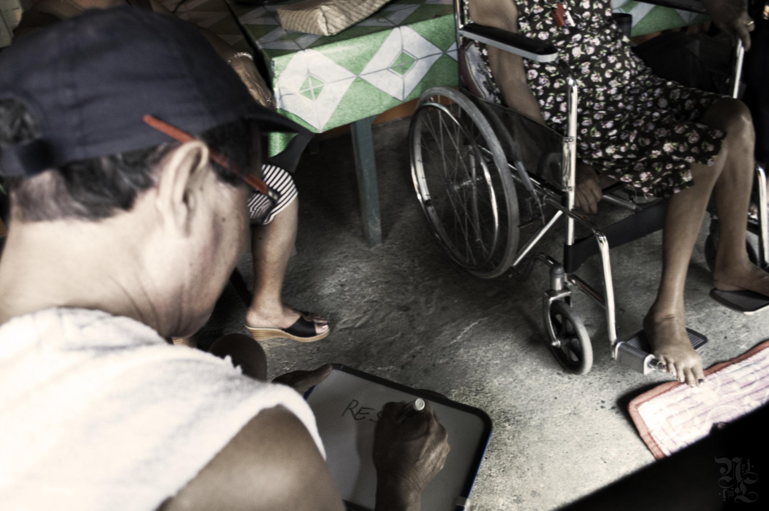 Man dictates dialogue to an elderly, deaf woman