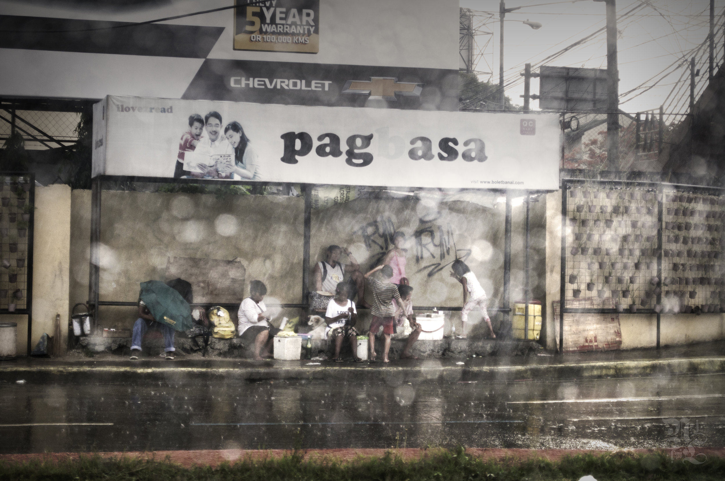 """Family of street beggers sitting under """"pag asa"""" (""""hope"""") sign"""