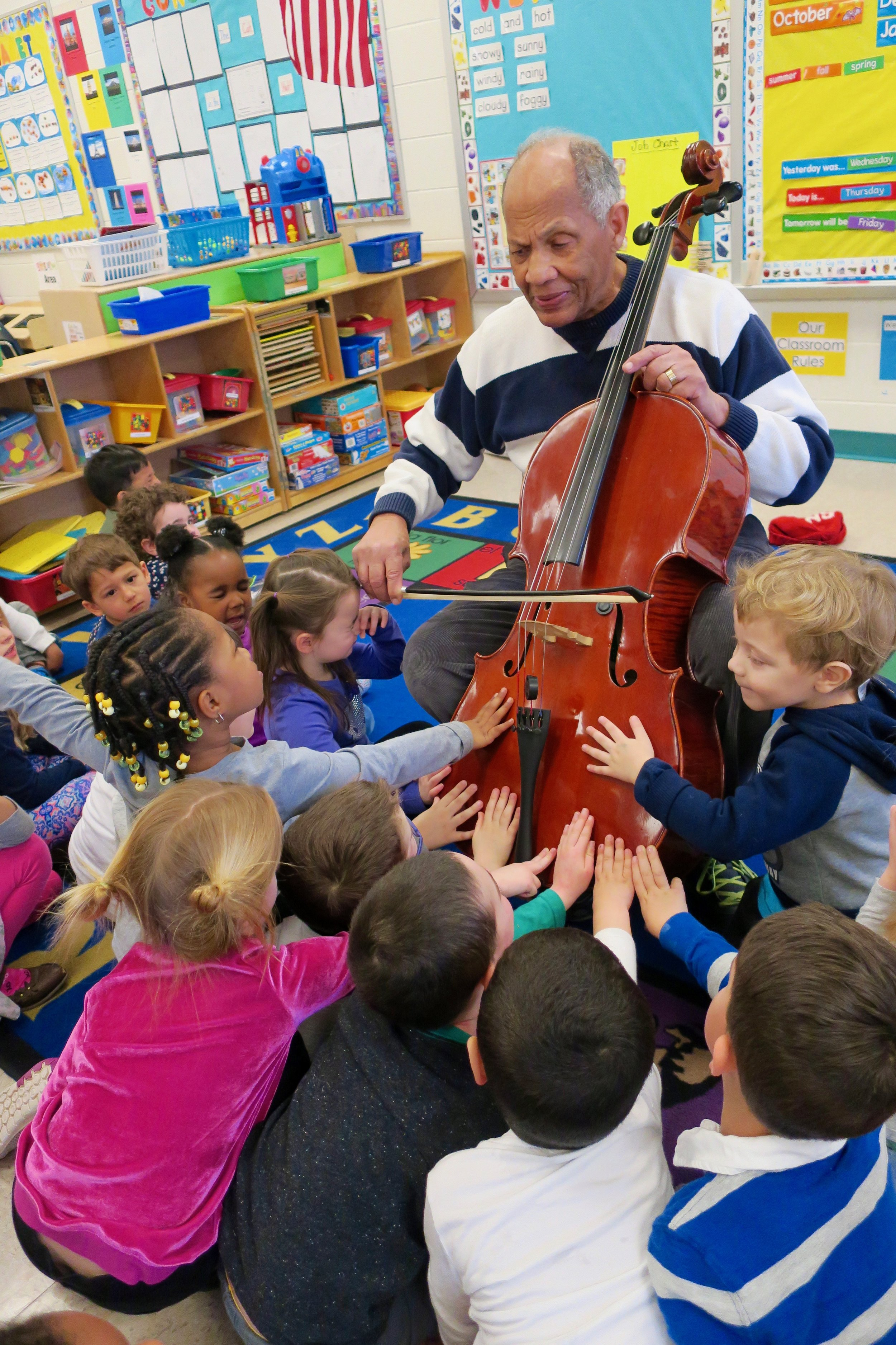 DC Strings Member Ray Pitts shares a moment with local elementary school children - sharing the joys of music and introducing them to the cello!