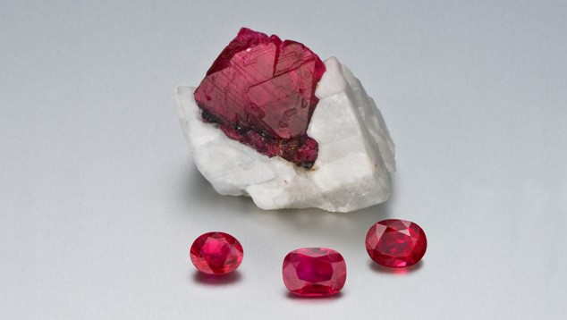 Various styles of cut ruby, together with a rough ruby crystal in a marble host rock. Rubies found in marble are more likely to show fluorescence than those found in basaltic rocks containing iron - which inhibits fluorescence. Photo credit: GIA