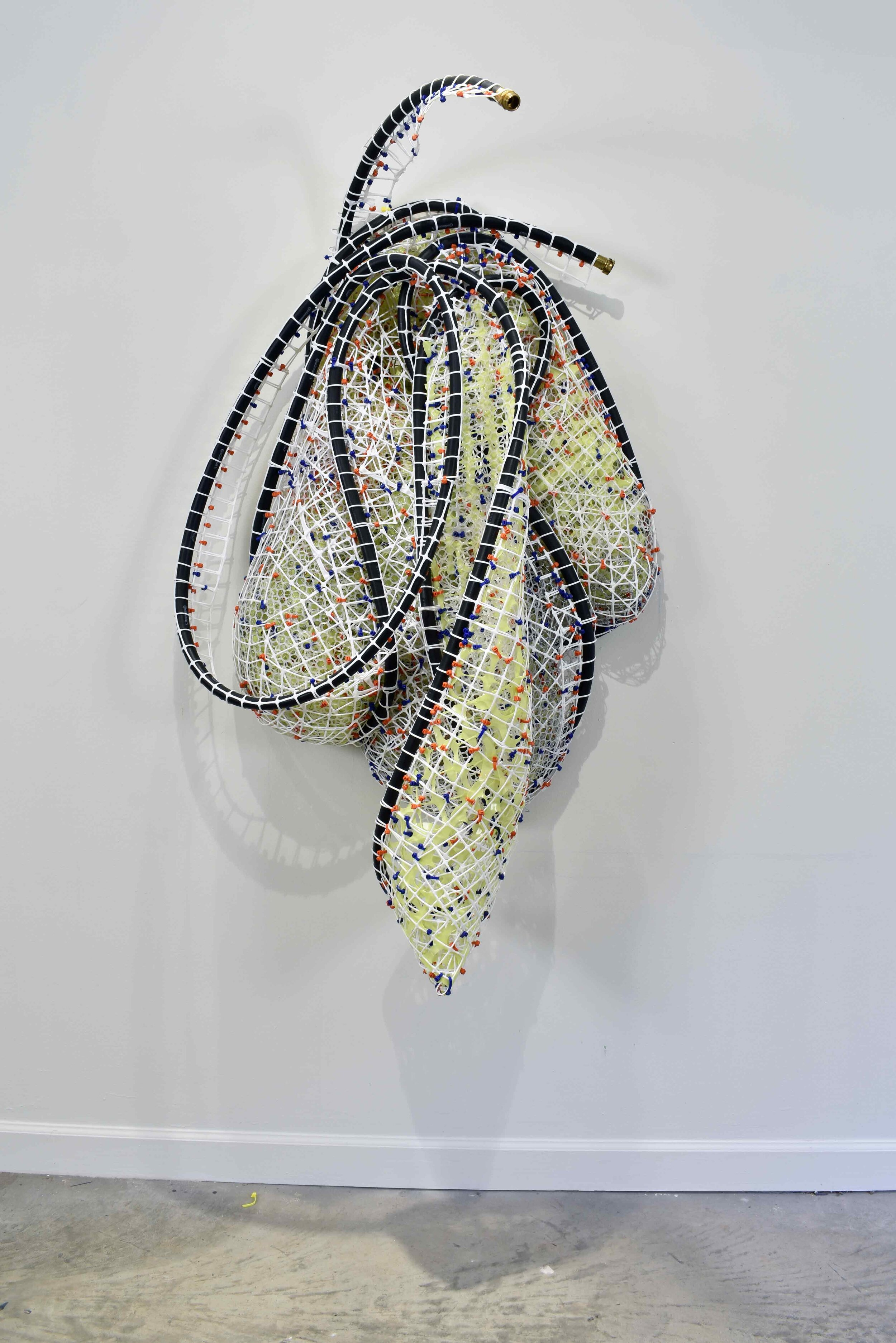 """Kryptonite Hose_1   2019  plastic and metal fencing, cable ties and rubber hose  60 X 32 X 19"""""""