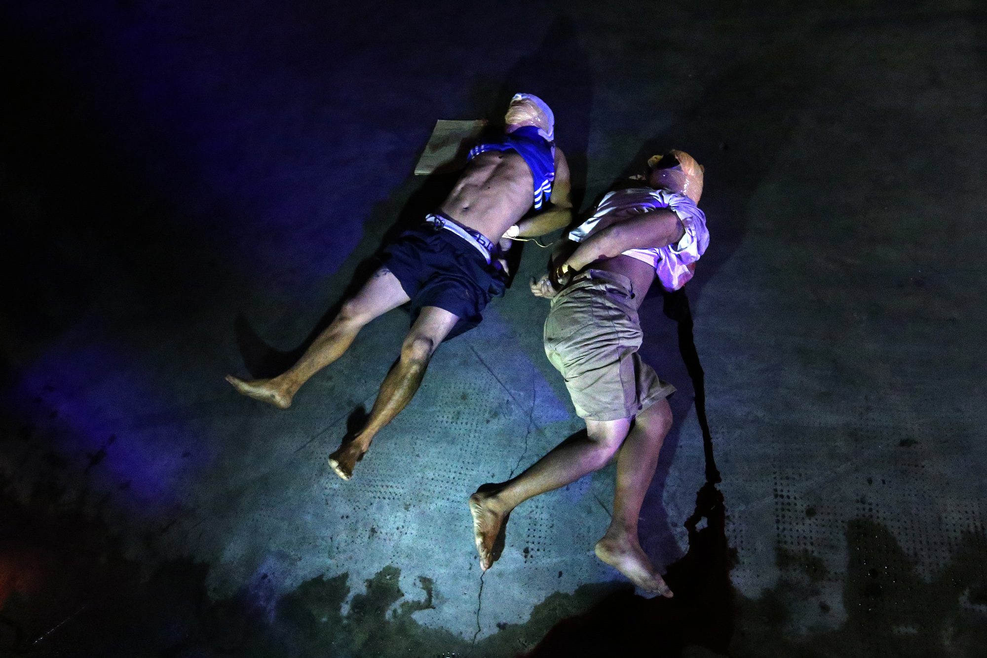 """Two victims of summary execution are dumped in front of Sta. Catalina College, Manila on October 4, 2016. A cardboard left near the victims' bodies called them drug pushers, holduppers and """"akyat bahay"""" gang members."""