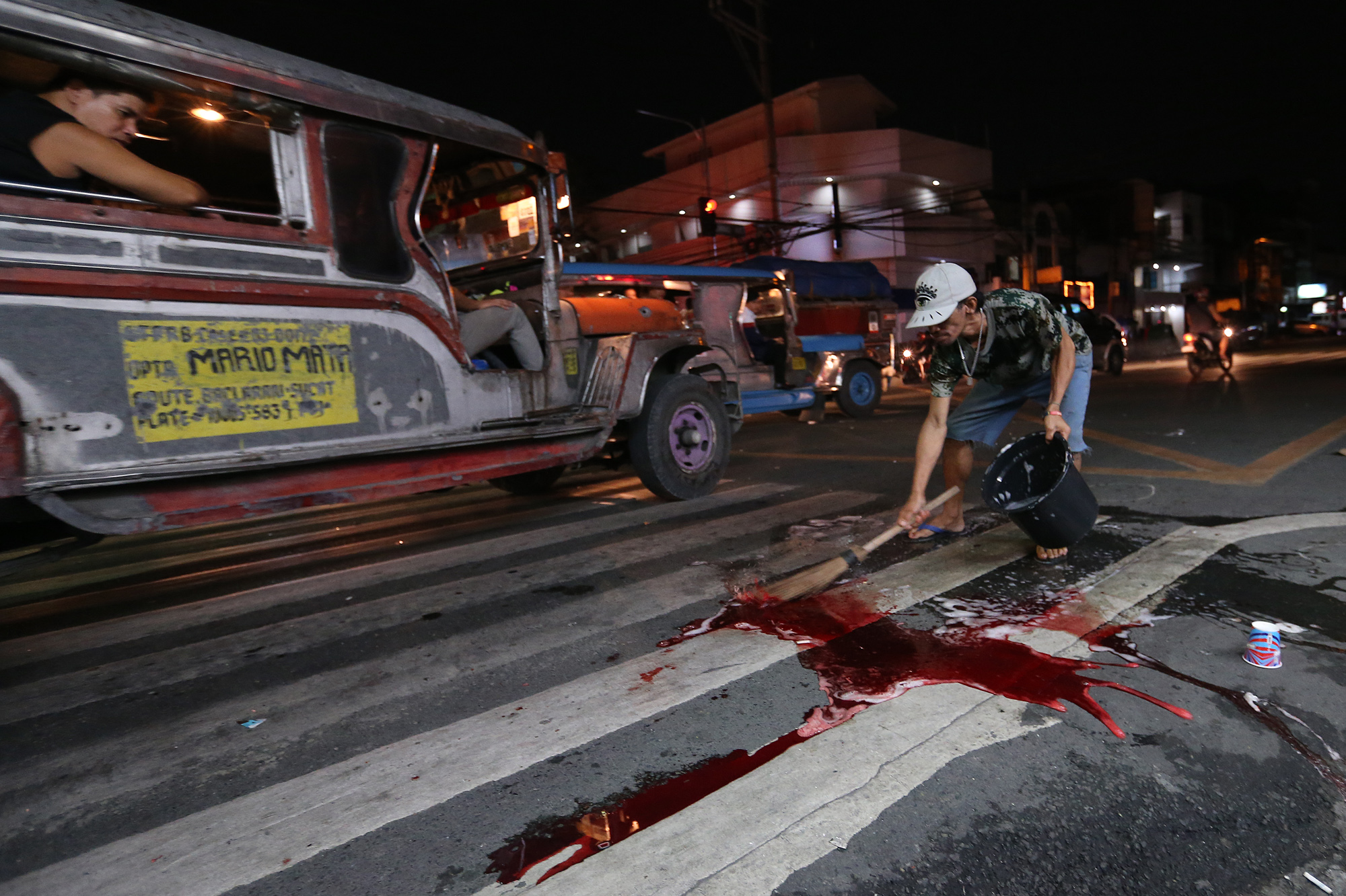 Blood from alleged drug user Edwin Mendoza, a barker who was shot by still-unidentified person is cleaned from the streets of Barangay Tambo, Paranaque on October 18, 2016.