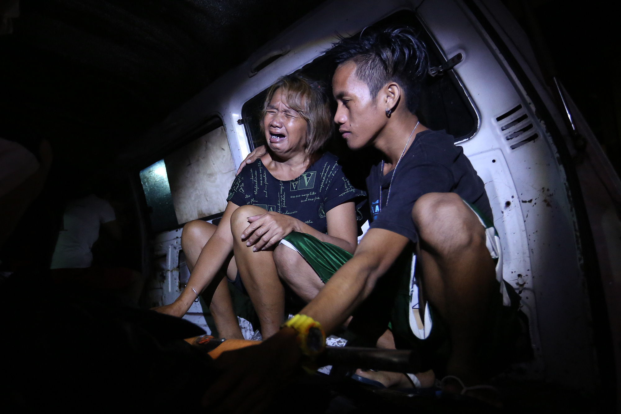 Nellie Diaz, wife of alleged drug user and runner Crisostomo Diaz grieves beside the body of her husband who was killed by masked men inside his house in Dagat-dagatan, Caloocan on August 12, 2016.