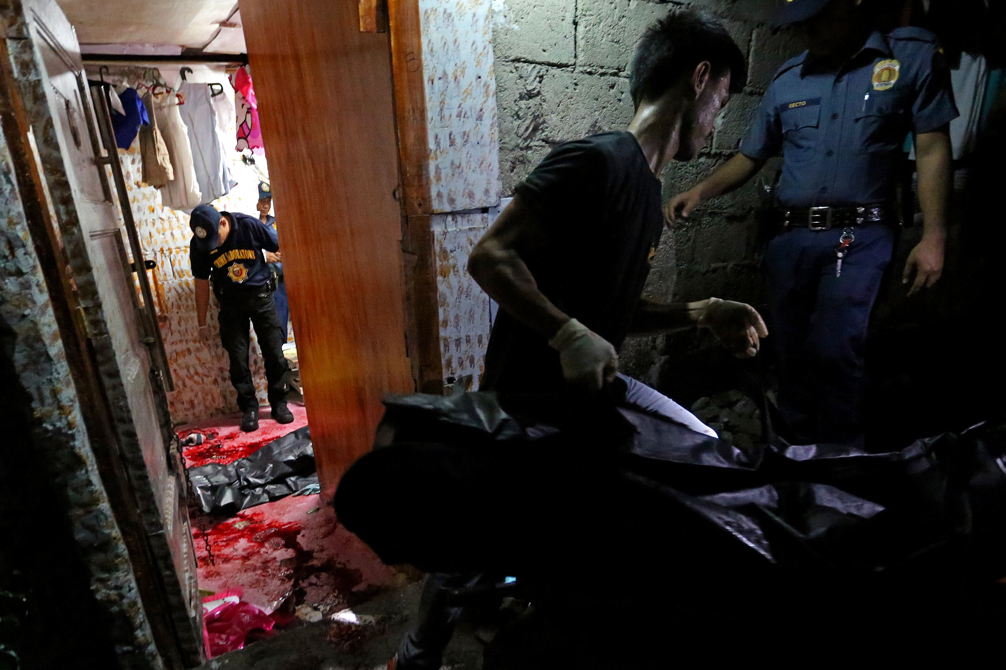 One of the four people in a drug buy-bust operation in Barangay Bagong Pag-asa, Quezon City is brought out by a coroner on October 25, 2016.