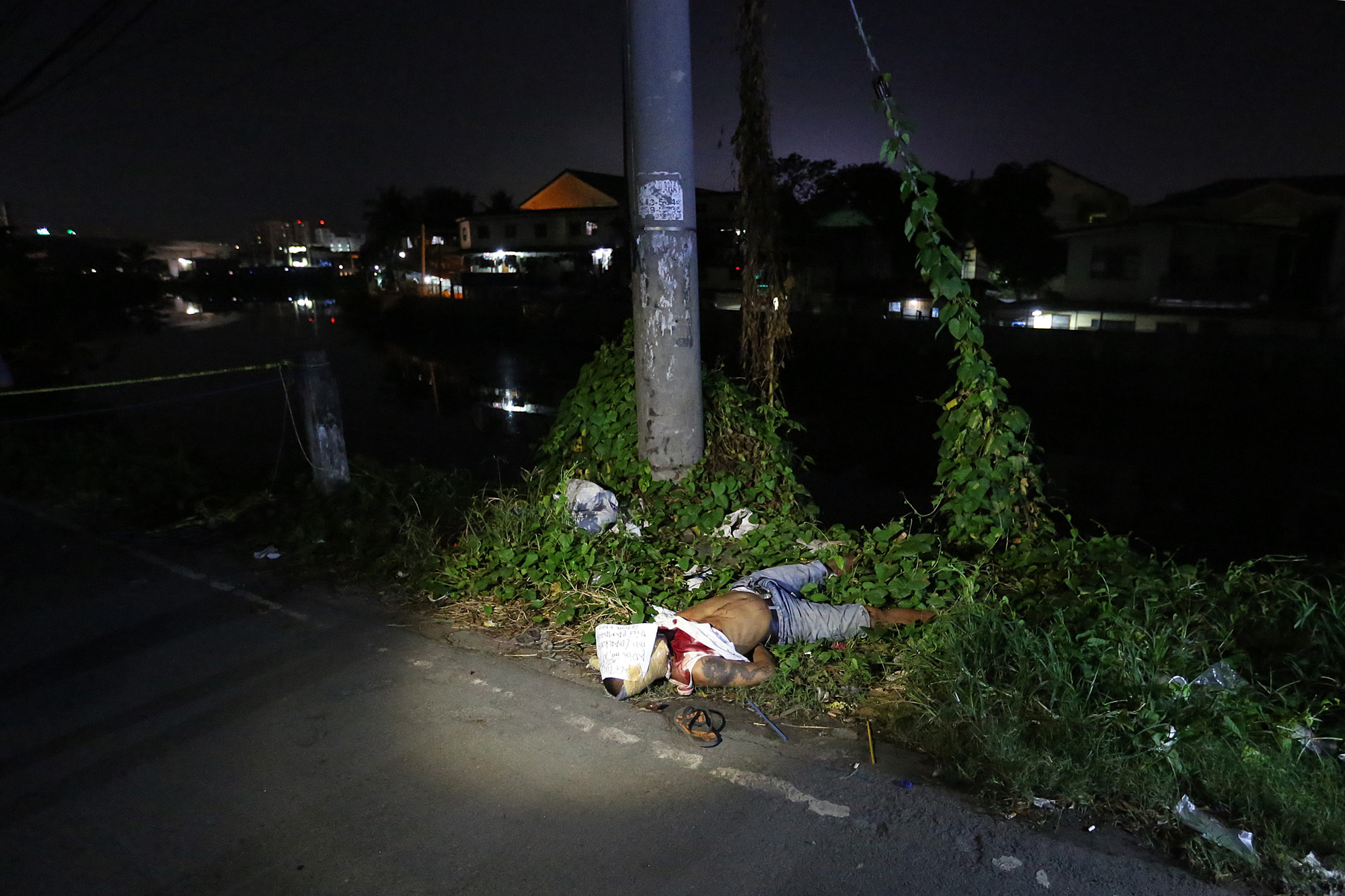 A police investigaor inspects a victim of summary execution dumped in Don Carlos Street, Barangay 190, Pasay City on November 16, 2016. A total of eight summary execution victims were found in Pasay and Makati City on the same night.