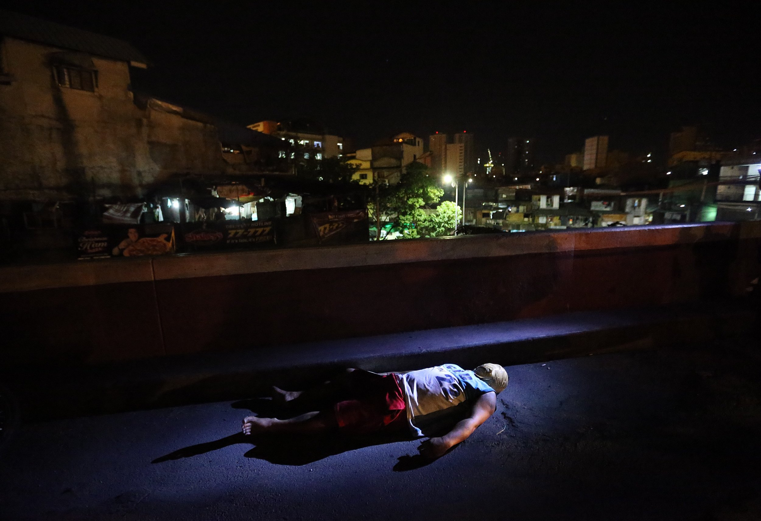 """On November 22, 2016, yet another victim of summary execution was found at Delpan Bridge, Tondo, Manila. His face was covered in packaging tape, while a cardboard sign left beside his body wrote """"drug pusher ako, huwag tularan."""" (""""I am a drug pusher, do not tolerate me."""") Minutes into the crime scene, his family arrived to identify him as Rene Desierto."""