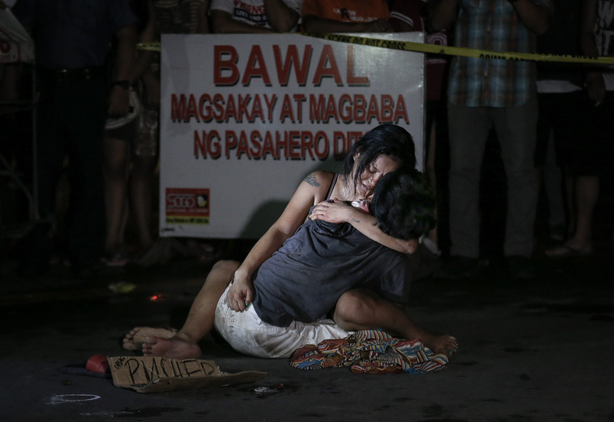 """Jennilyn Olayres holds her partner Michael Siaron, 30, a pedicab driver, who was shot and killed by unidentified riding in tandem suspects along LRT Pasay Rotonda, Edsa on July 23, 2016. A placard was left beside the victim's body with words, """"Pusher ako, wag tularan."""" (I'm a pusher, do not copy me.)"""