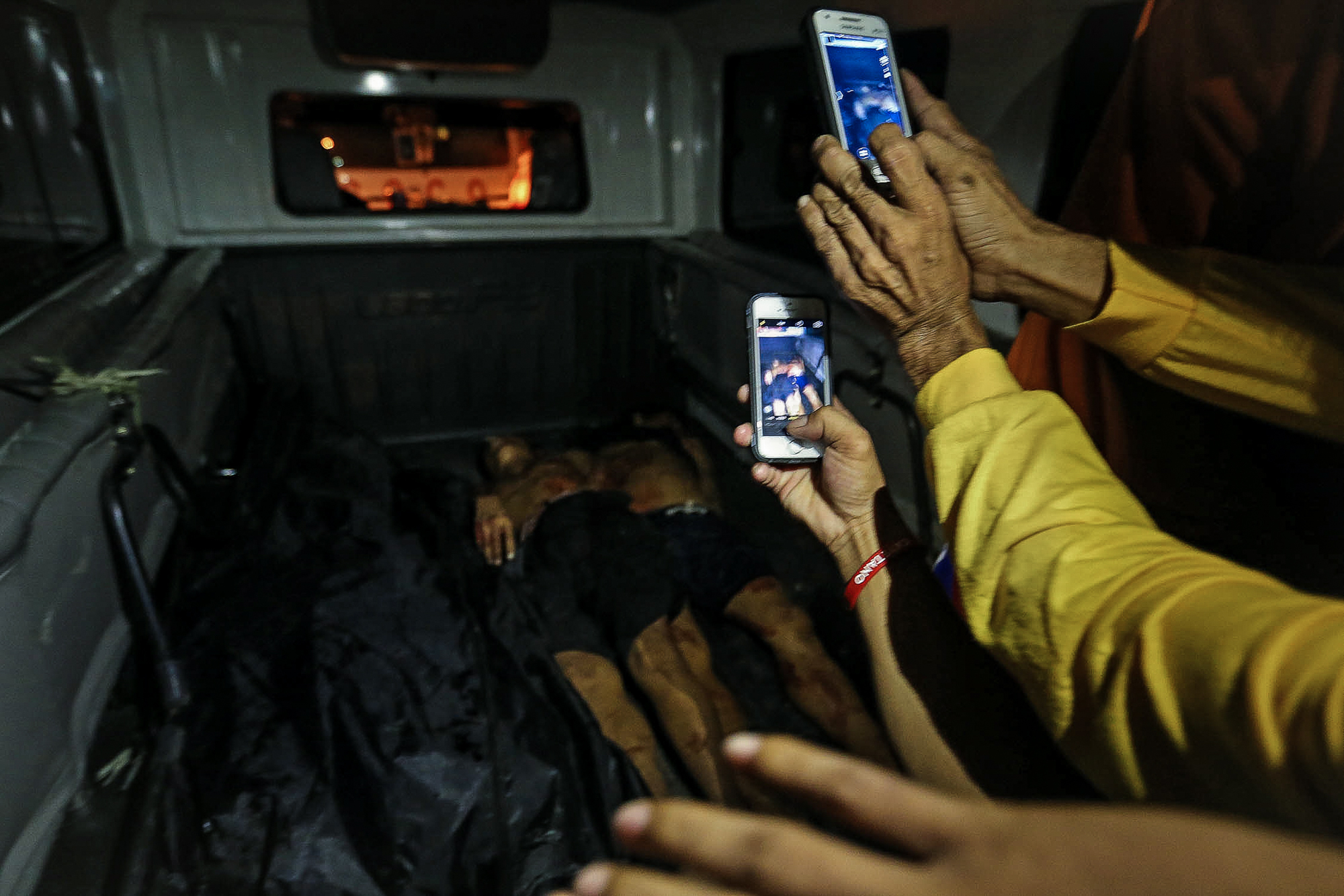 Onlookers take photos of the dead bodies of three alleged drug dealers killed during a buy bust operation in Cahilom corner Apitong St., Barangay 872, Pandacan, Manila on July 16, 2016.