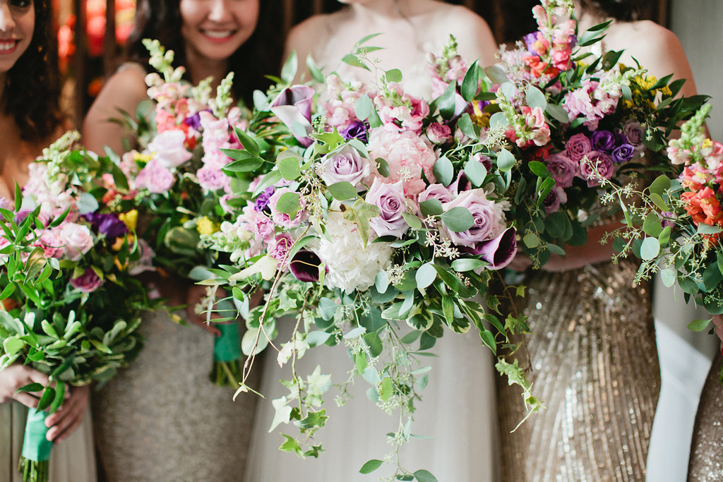 Mixed metallic bridesmaid dresses and organic bouquets. Photo by Sasithon Photography.