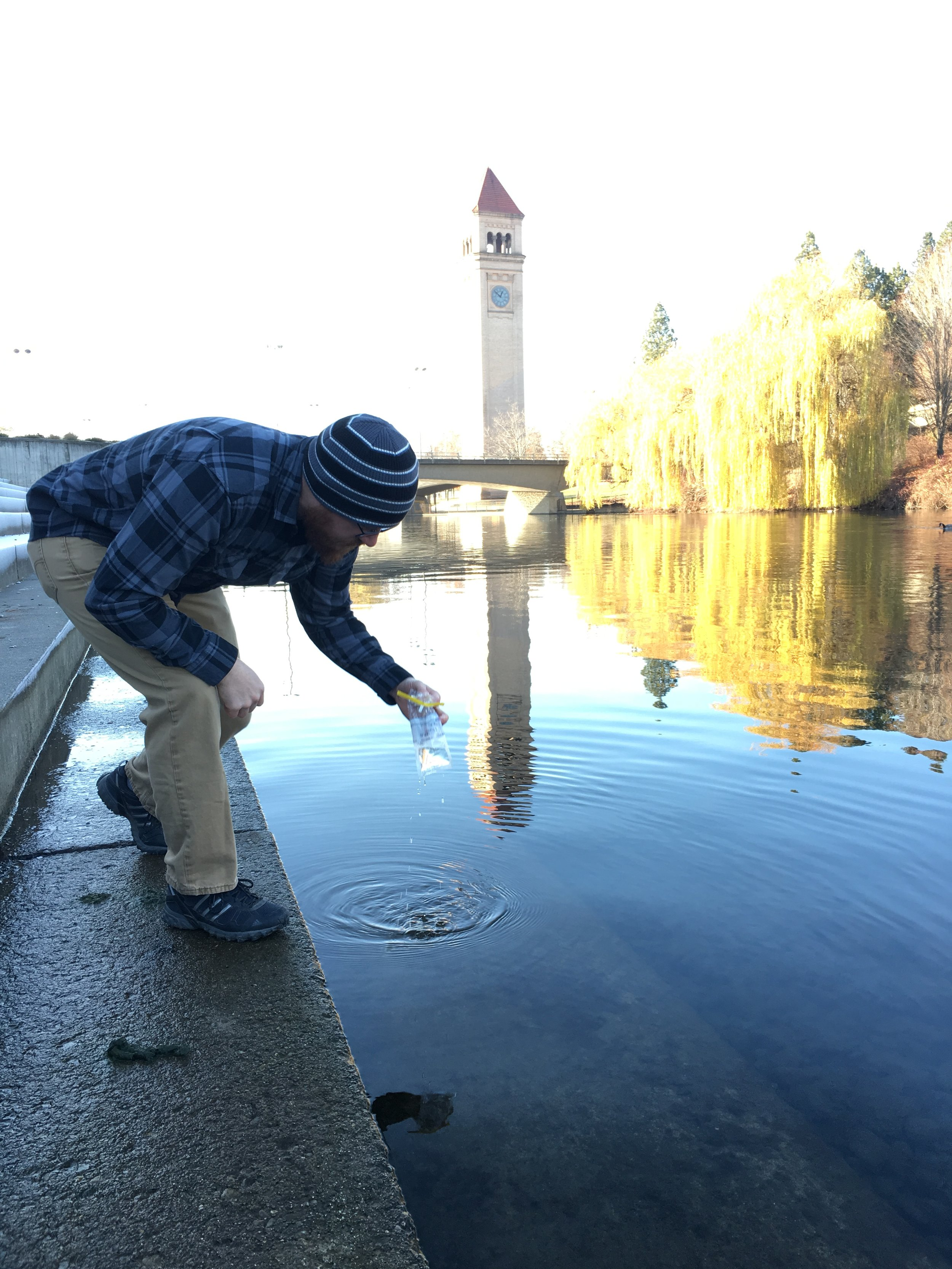 Dillon Wilke collects a fecal coliform sample in the Spokane River