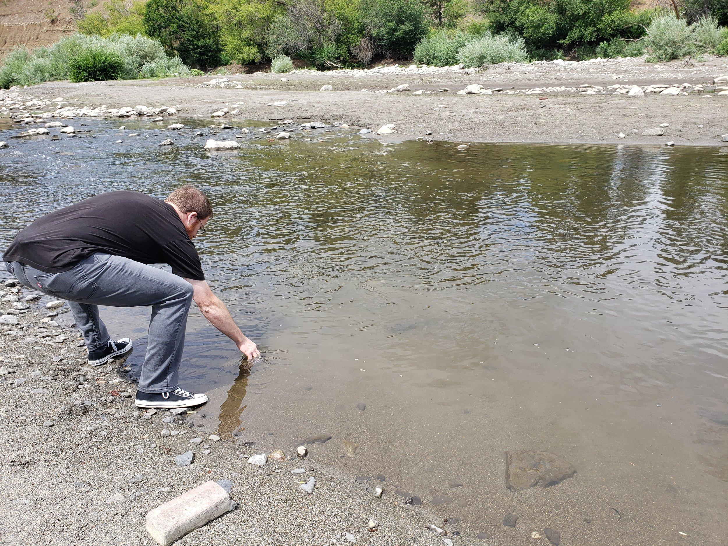 Dillon Wilke takes a water sample for  E. coli  at Hangman Creek.