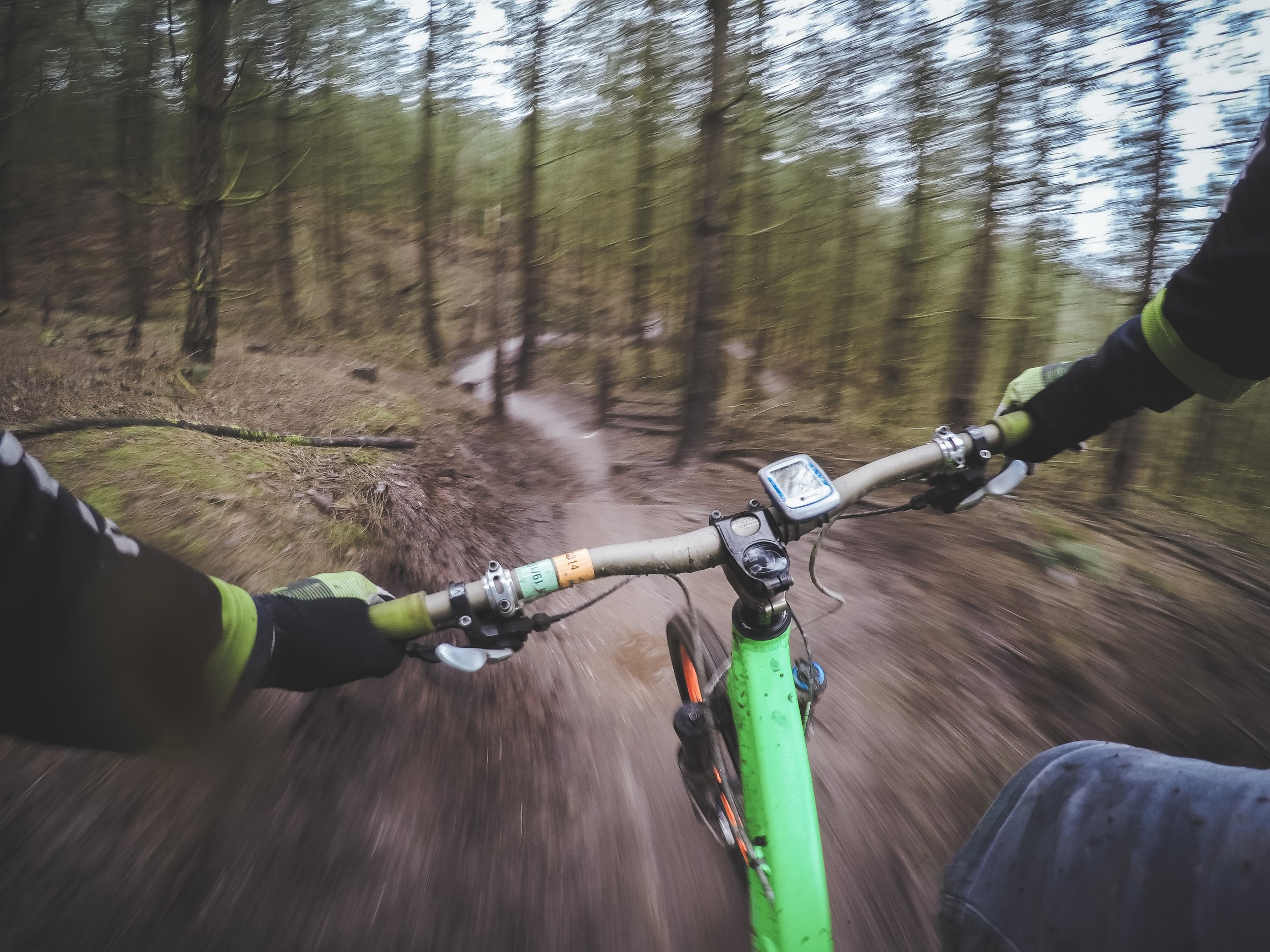 Photo of a dude on a bike ripping down a trail.
