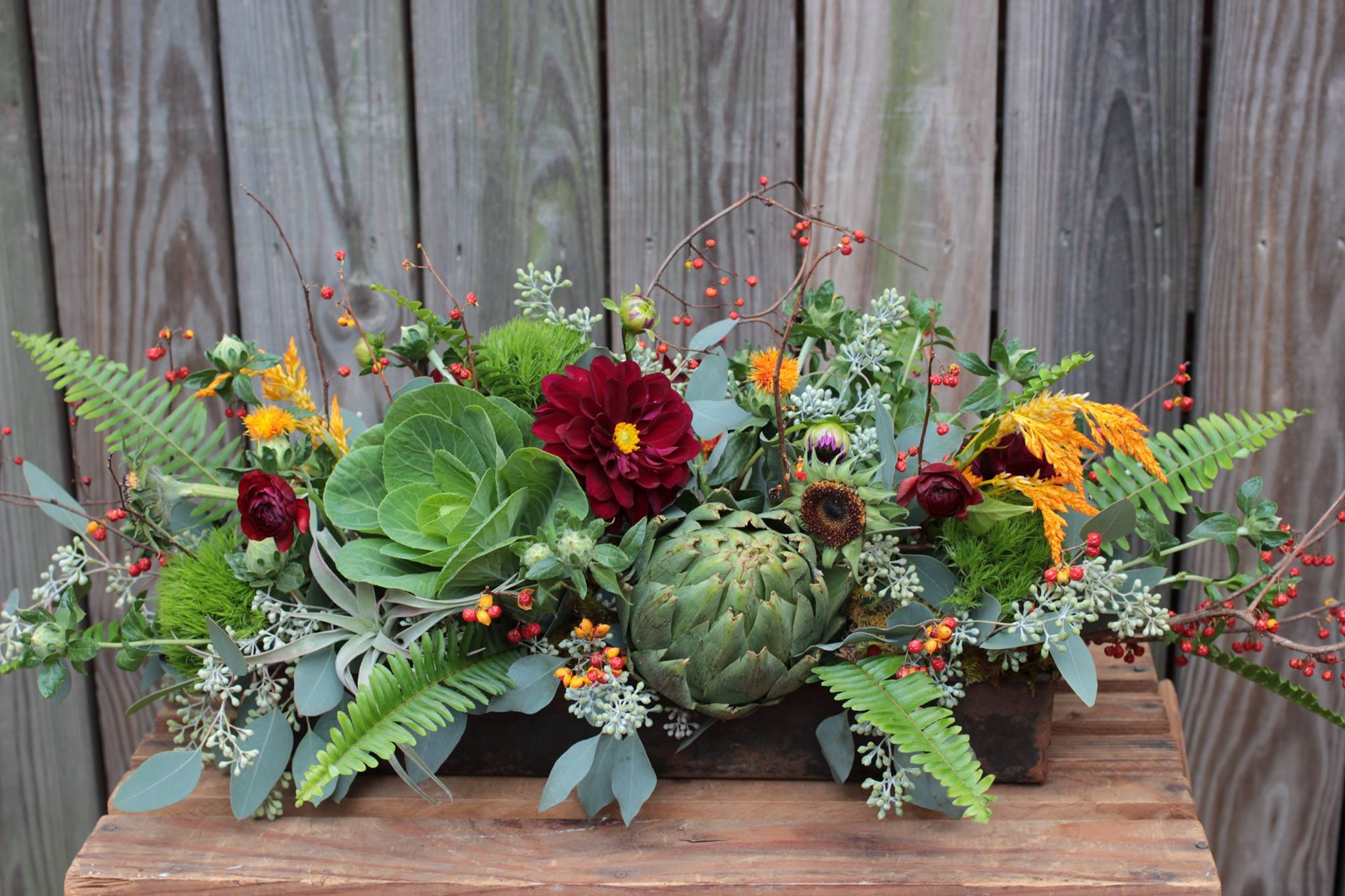 An arrangement featuring artichoke, cabbage, bittersweet, dahlias among others.