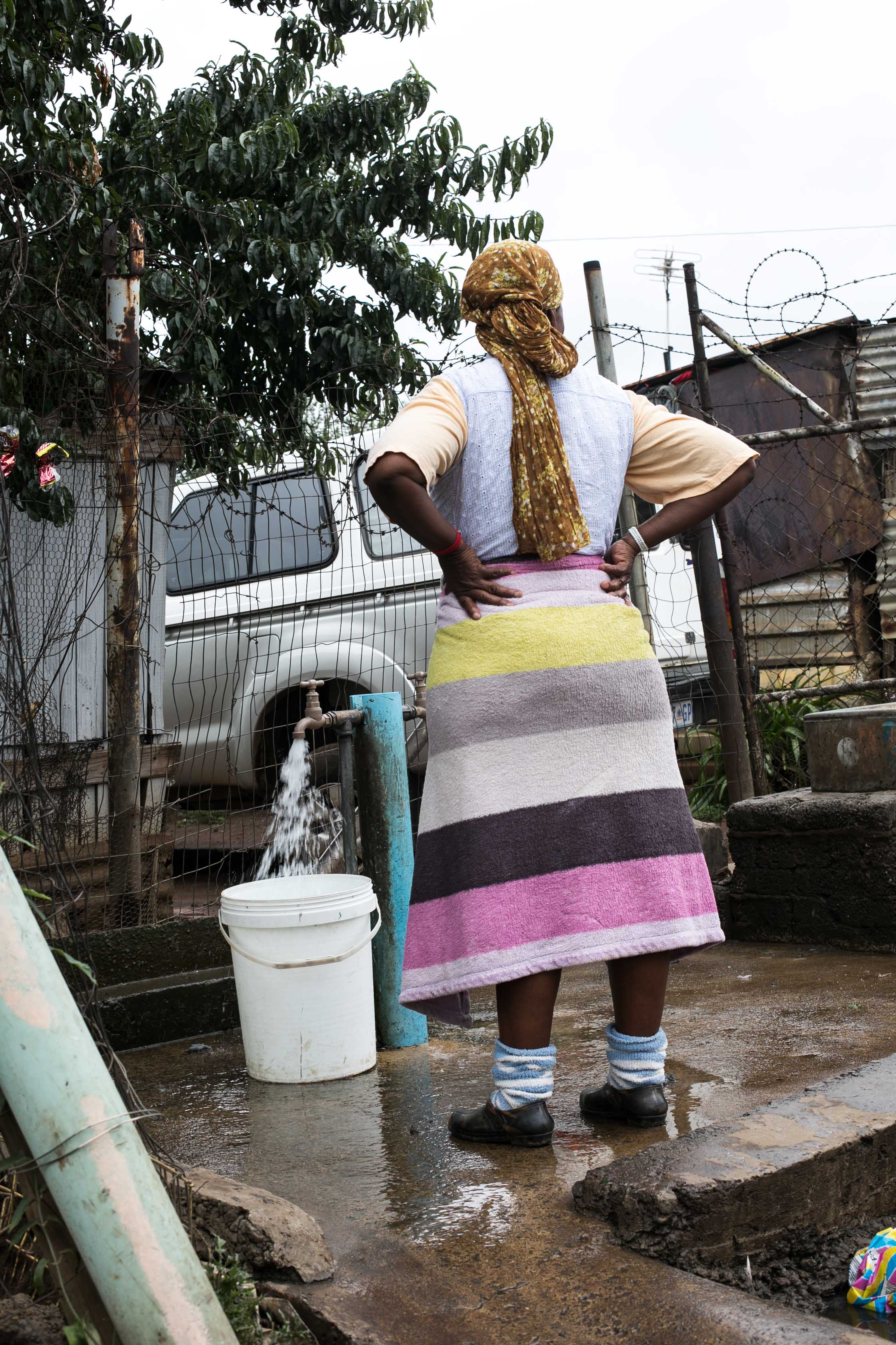 A woman standing at a communal water station shared by thousands of other residents in a community in Soweto.