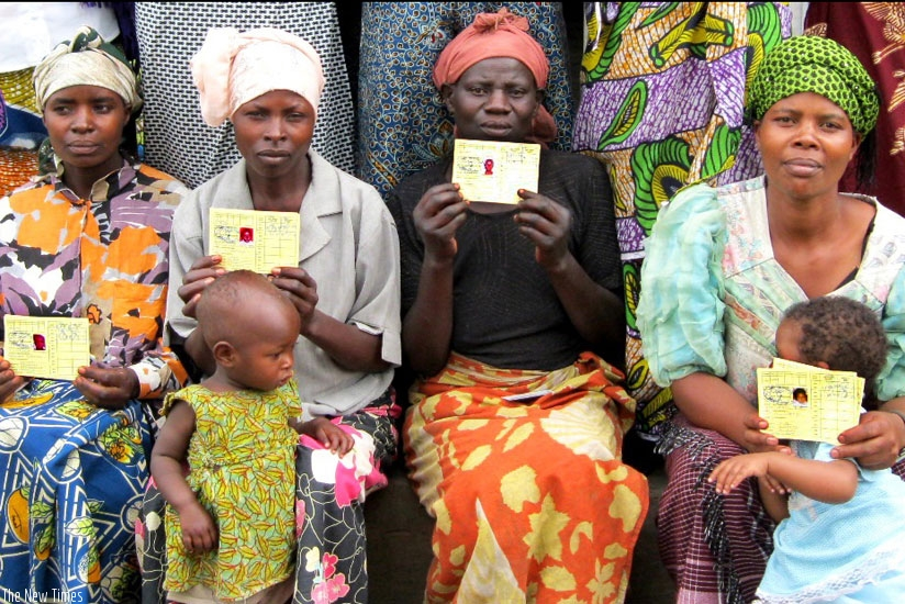 Mothers pose with their health insurance cards at a health centre in Kicukiro District