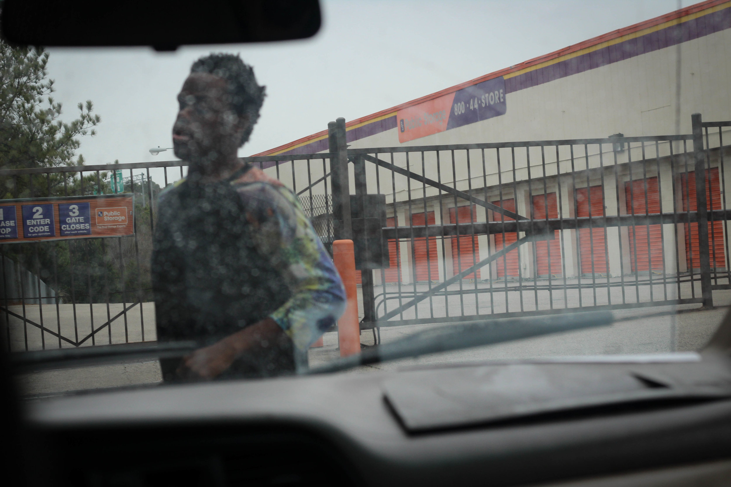 """Equashia's son, Abdurrahman, opens the gate to enter the storage facility where Equashia is storing the items that won't fit in her van and hotel rooms. """"Ever since he got shot, he's got this chip on his shoulder,"""" says Equashia. Shortly after the shooting, Abdurrahman purchased a gun and began carrying it around with him at all times for protection. Out of anger, he talks about shooting the people who did this to him. """"I lost a son to gang violence in 2011,"""" says Equashia. """"These boys don't know what it's like to have to get that call, to have to identify your child. They talk about shooting so casually."""""""