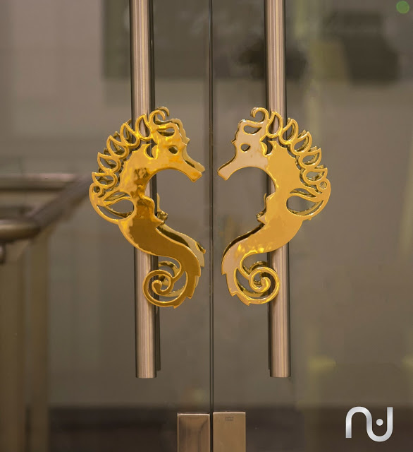 Deema Oman's logo executed in brass finish and used as door handles.