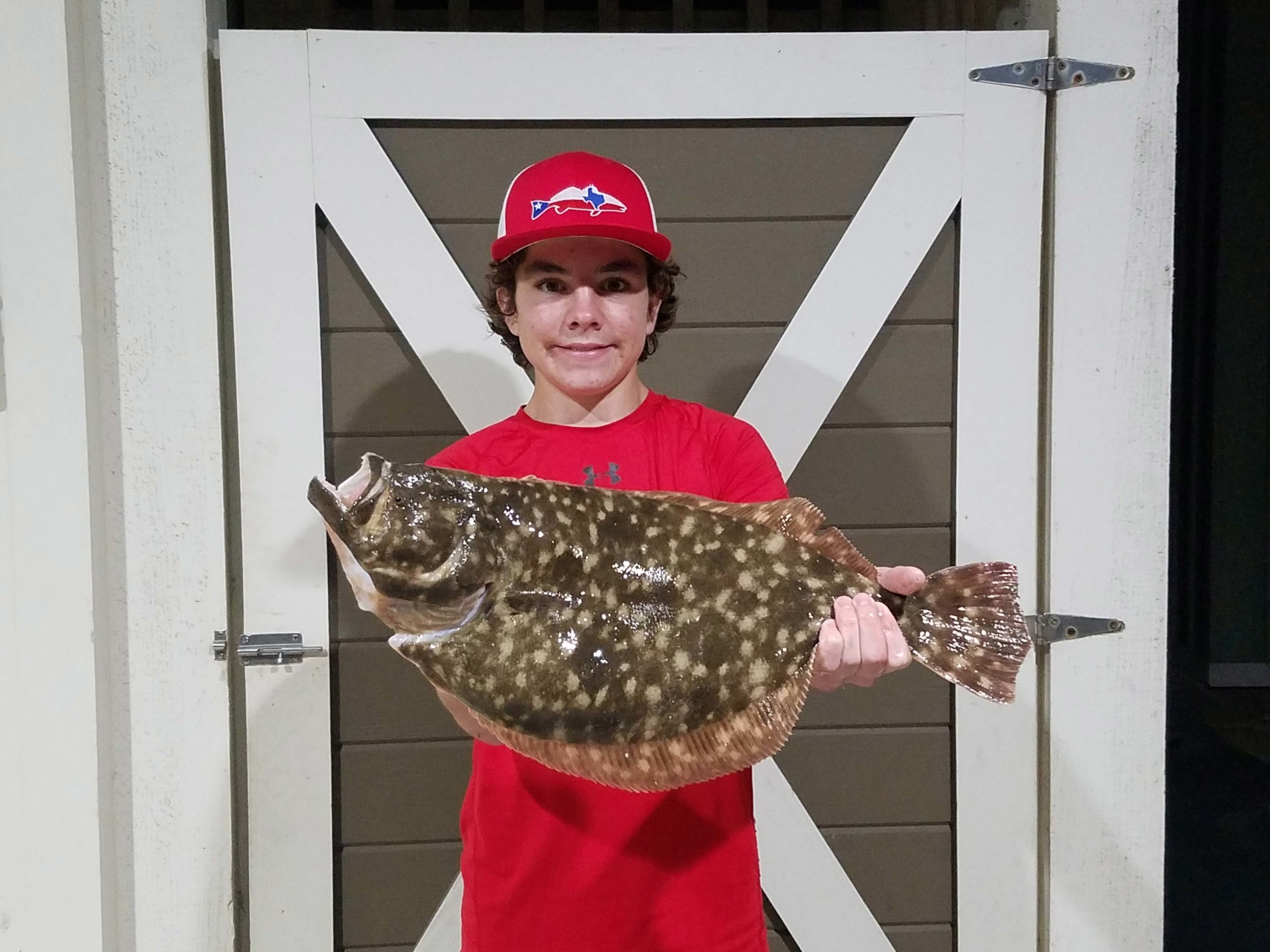 One of resident's sons with a trophy flounder caught in the canal behind his home in Laguna Harbor