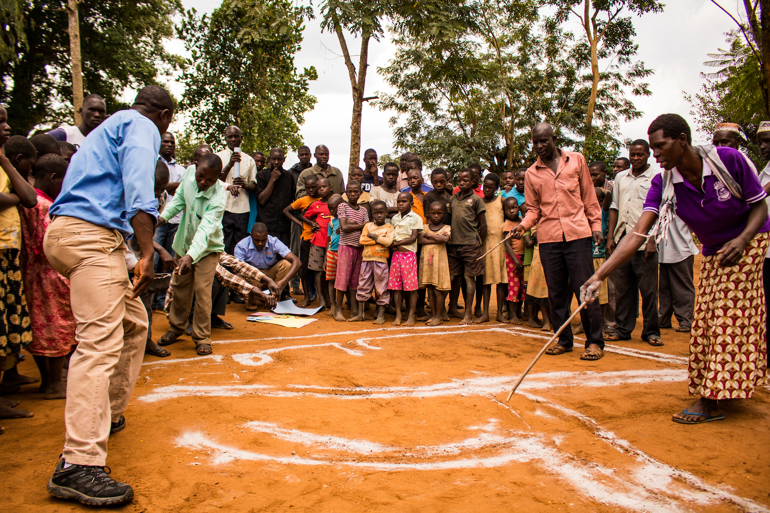 "After the walk of shame comes ""mapping."" As a group, the community uses ash to create a map of the village on the ground. Participation is crucial at this stage. Our staff uses the map to calculate population, latrine coverage and land ownership. Mapping shows that everyone's actions affect everyone else."