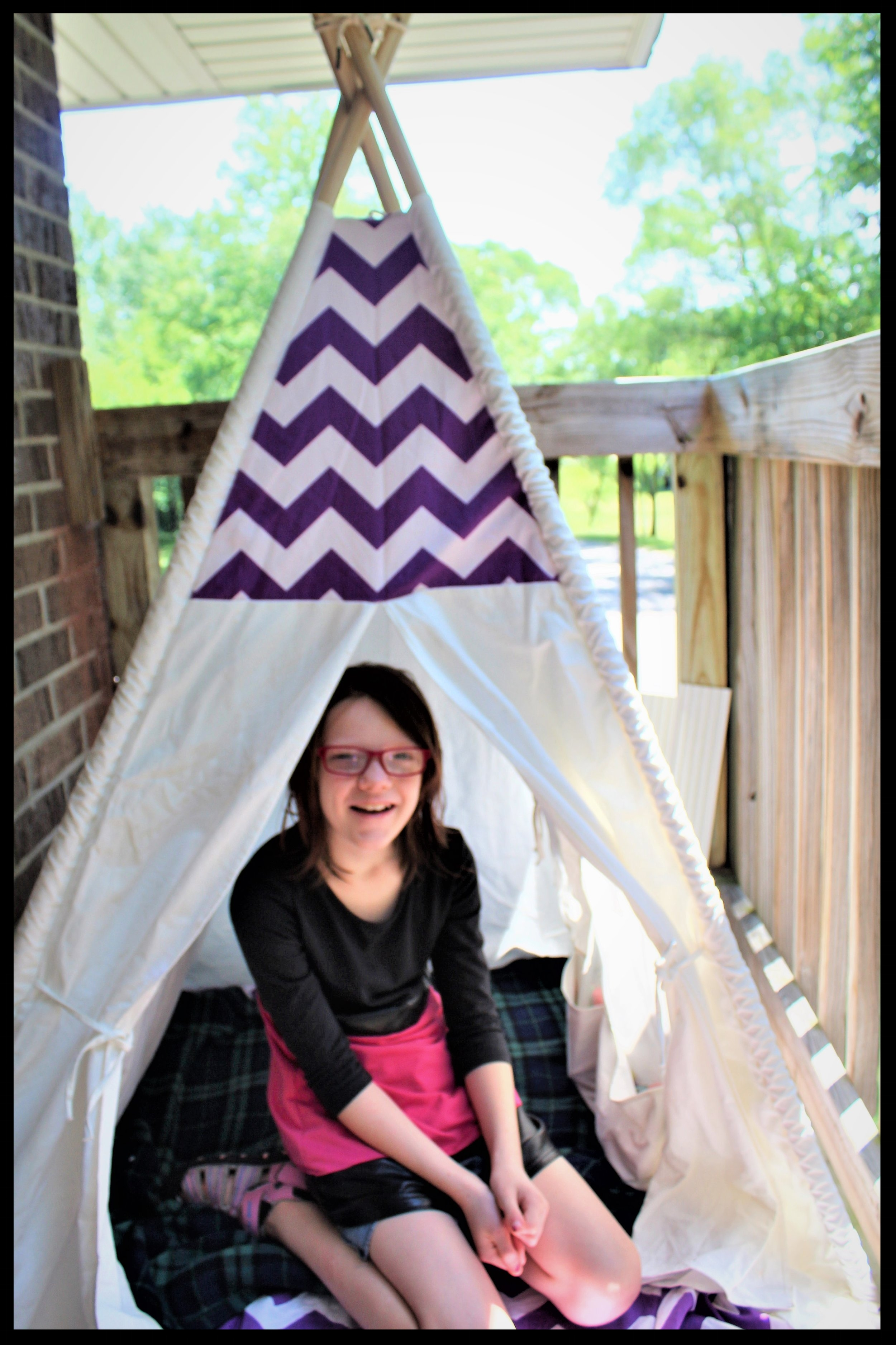 As you can see Bella was very willing to take photos inside the teepee and loved her teepee so much that she was almost in tears. Bella has wanted a mini reading spot of her own for ages. Usually she reads on her bed or the couch this way she get's outside and enjoys the fresh air all while being comfy. I love that there is also room for a light so she can sit out on the deck at night and read too.