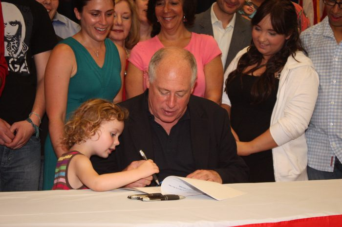 Illinois Governor Pat Quinn signs the  Prevent School Violence Act  into law. Behind, stands Founding Alliance Executive Director, Shannon Sullivan, and Alliance Youth Committee Members who advocated for the bill's passage.