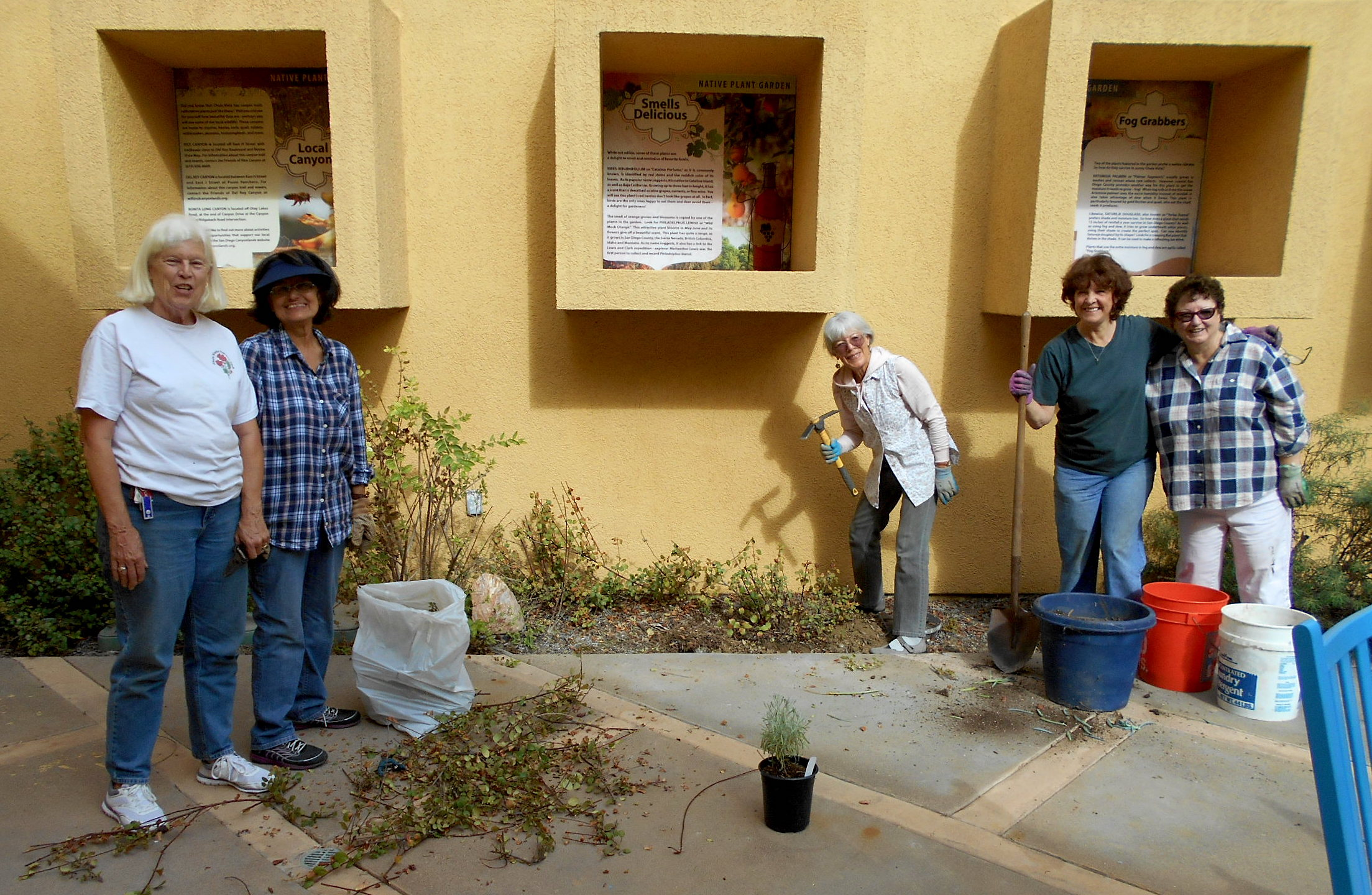 (L to R): Chris, Betty, Kay, Joan, and Emily plant and primp. The boxes over the plants have beautiful information posters.