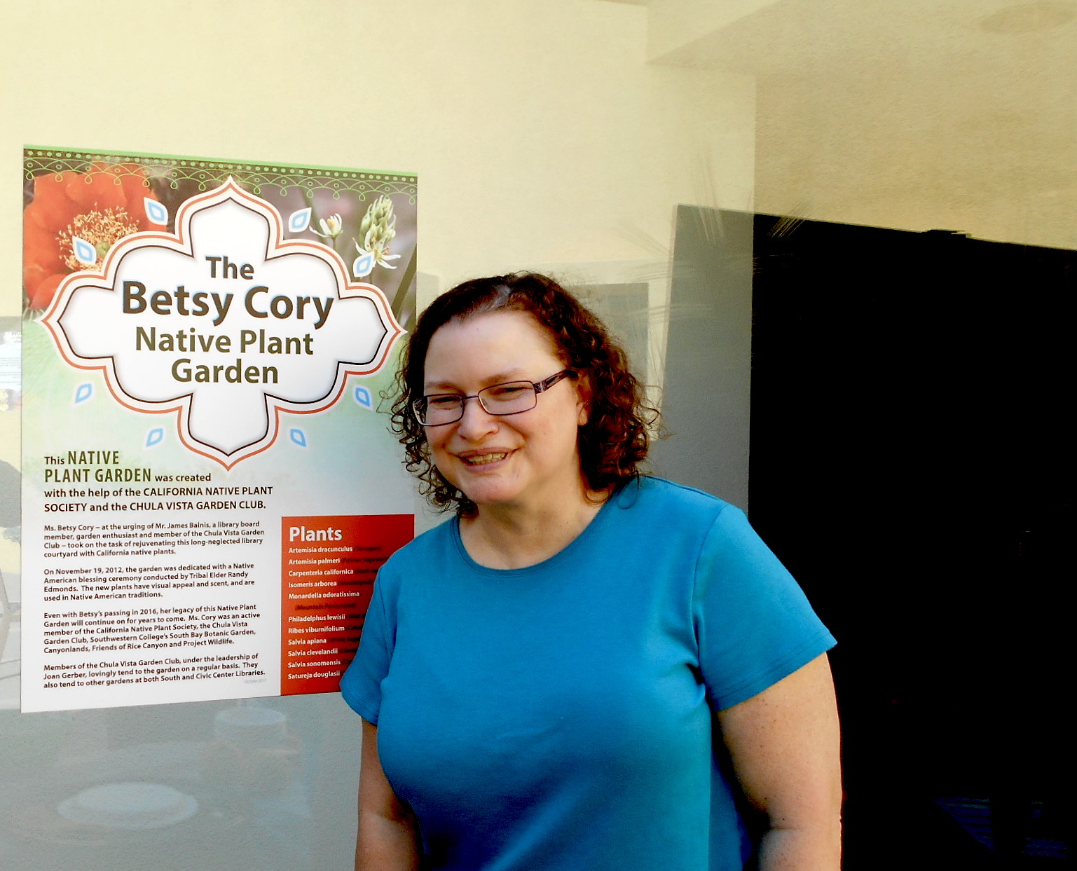 Robin, one of Betsy Cory's daughters, next to the Garden's sign.