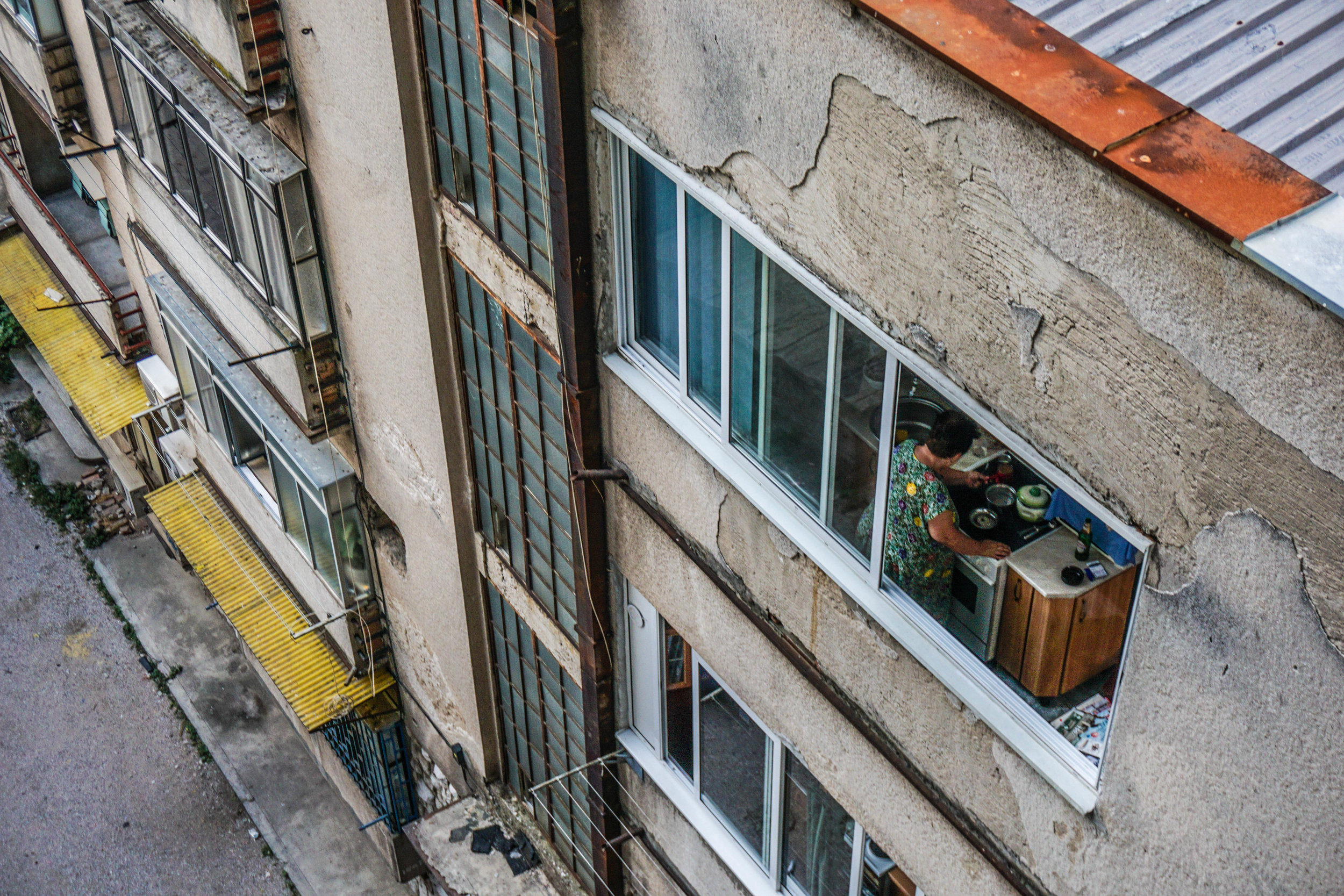 A woman cooks from her kitchen neighboring the Sniper Tower's main staircase by mere meters.
