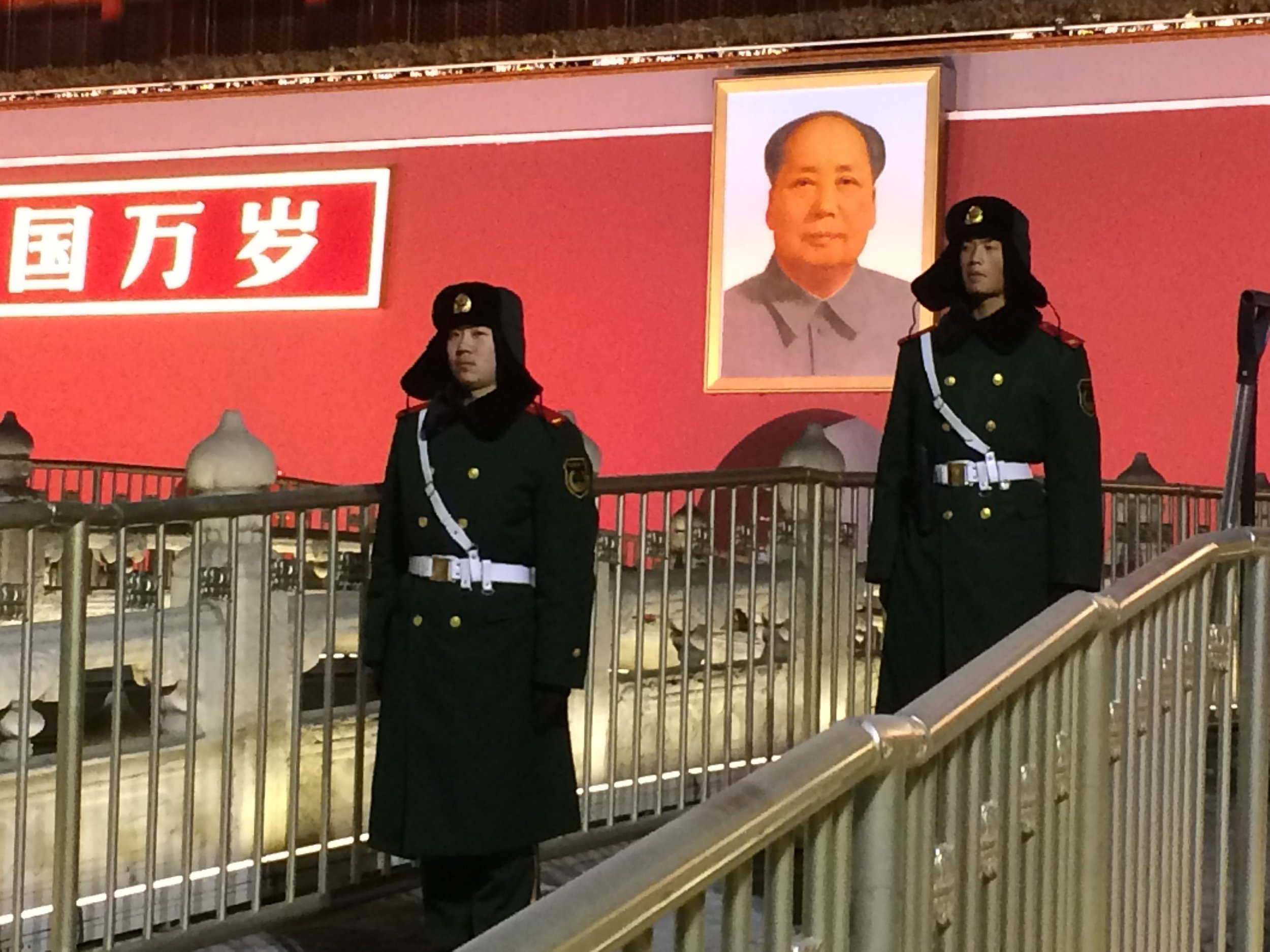 Guards beneath the portrait of Mao at Tiananmen Gate