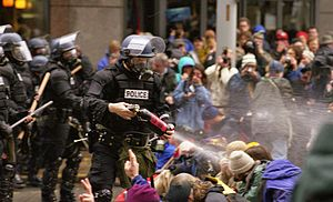 1999 rioters at World Trade Organization meeting in Seattle, November 30, 1999, under attack by police.