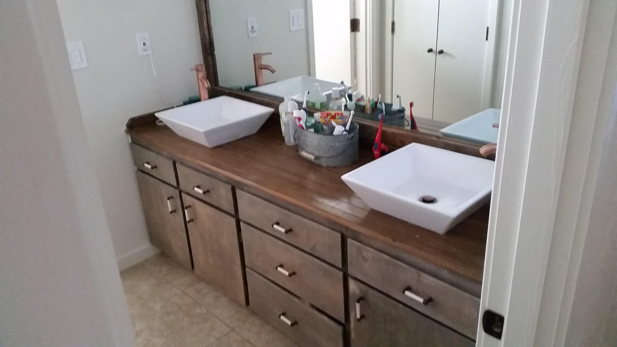 Refinished vanity with new top and basin sinks.
