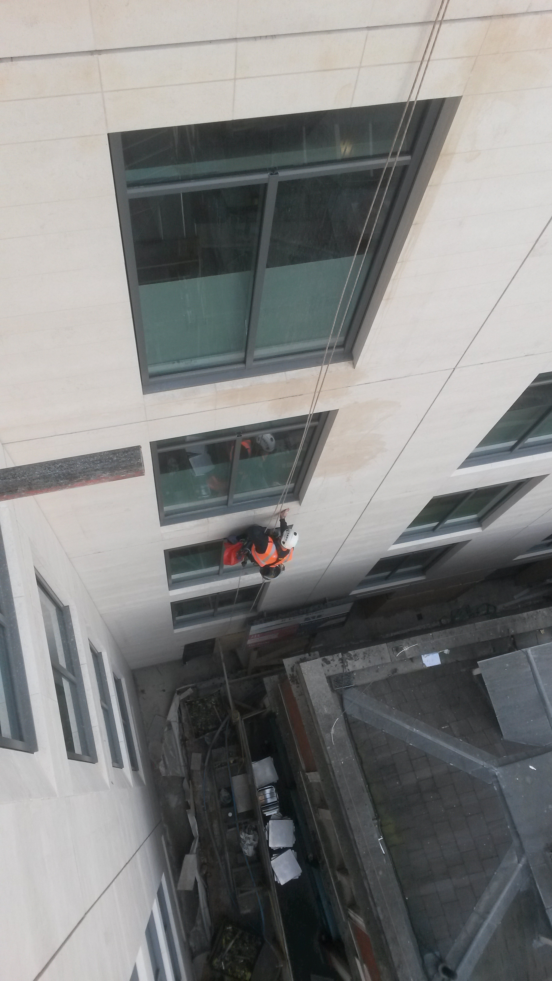 Abseiler carrying out rope access window cleaning