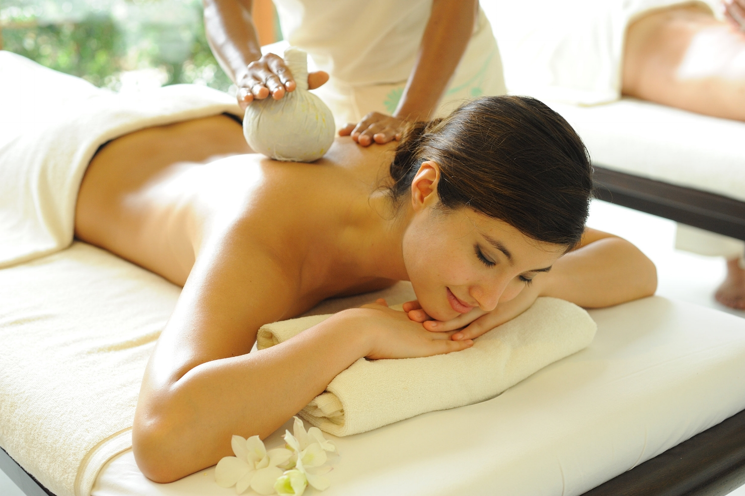 woman receiving thai-hot-steam-herbal-compress-massage with medical herbs during a thai body work session for deep therapeutic effects.