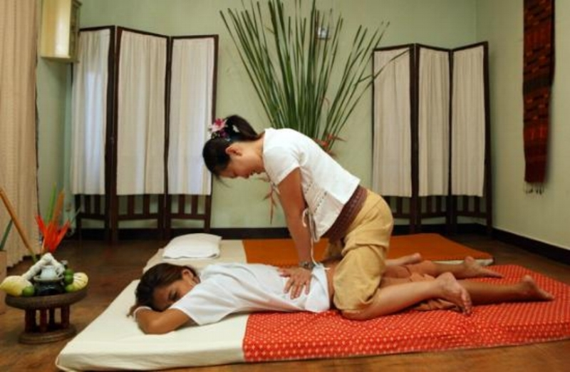 client receives authentic traditional thai massage from professional therapist.
